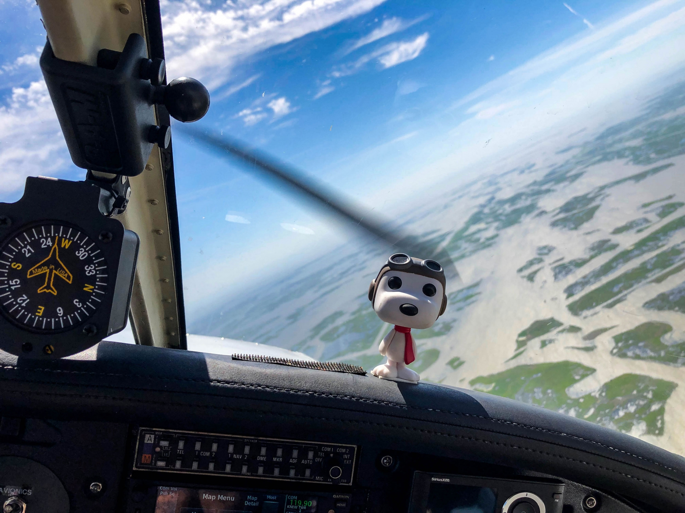 A figurine of Snoopy is shown on the dashboard of four-seat plane with aviator attire.
