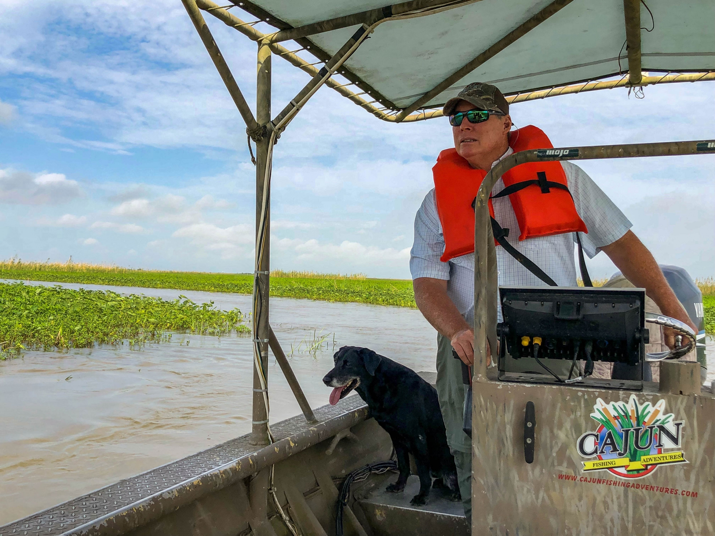Ryan Lambert is shown piloting a flat bottom boat with a dark colored dog sitting next to him.