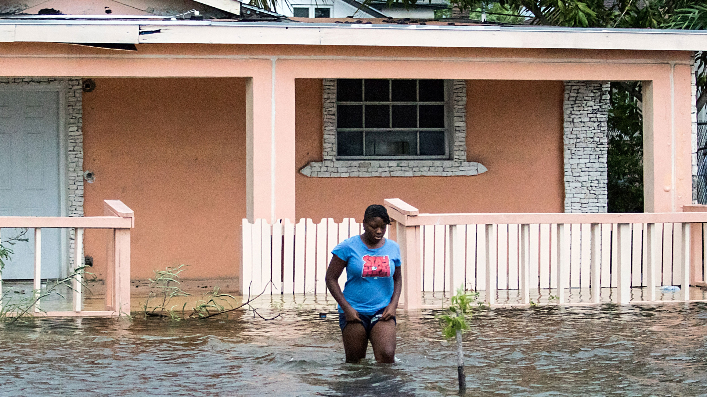 A woman is shown walking in knee-deep water in front of a peach-colored home.