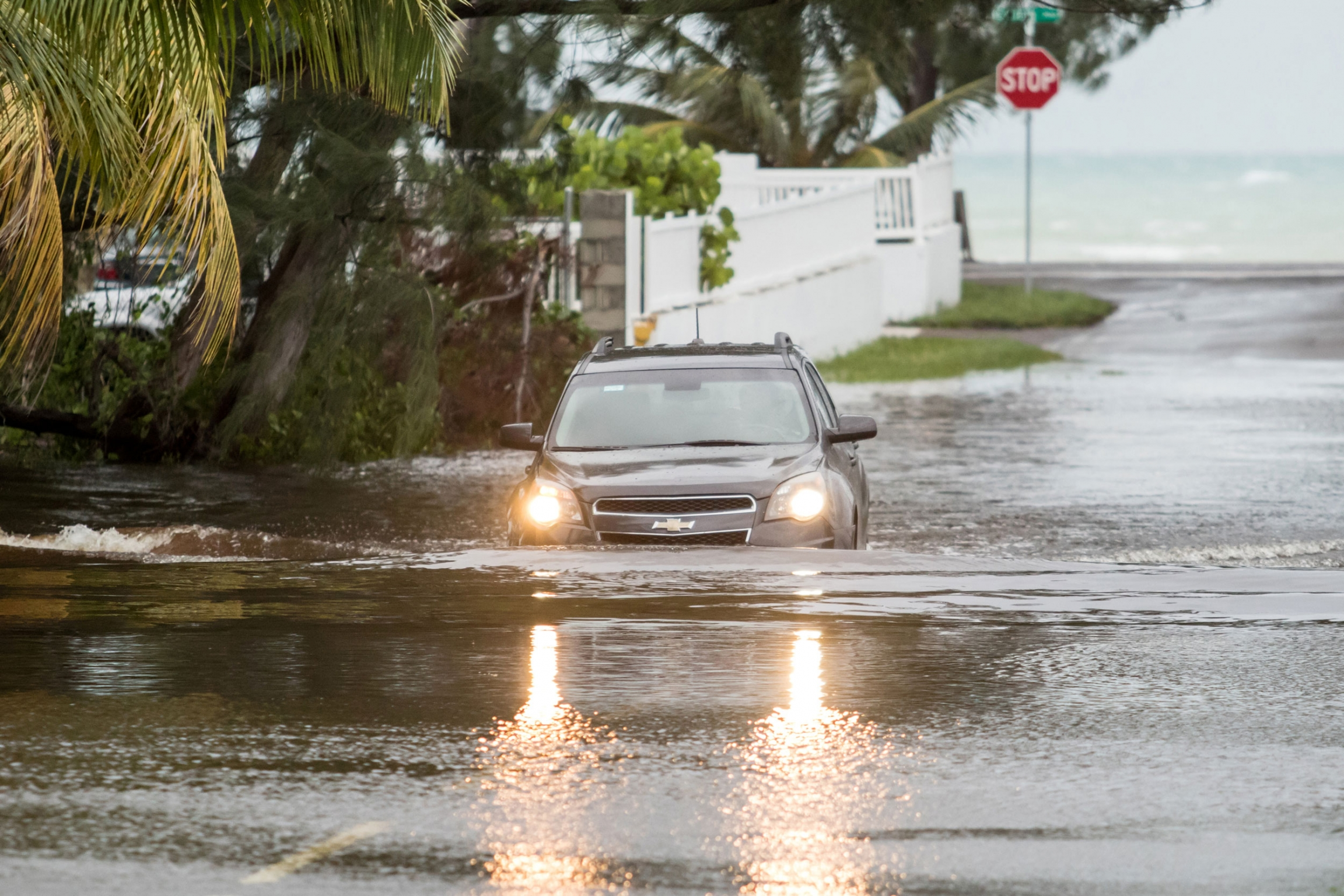 A Chevy SUV is shown driving with its lights on in a flooded street with water halfway up the tires.