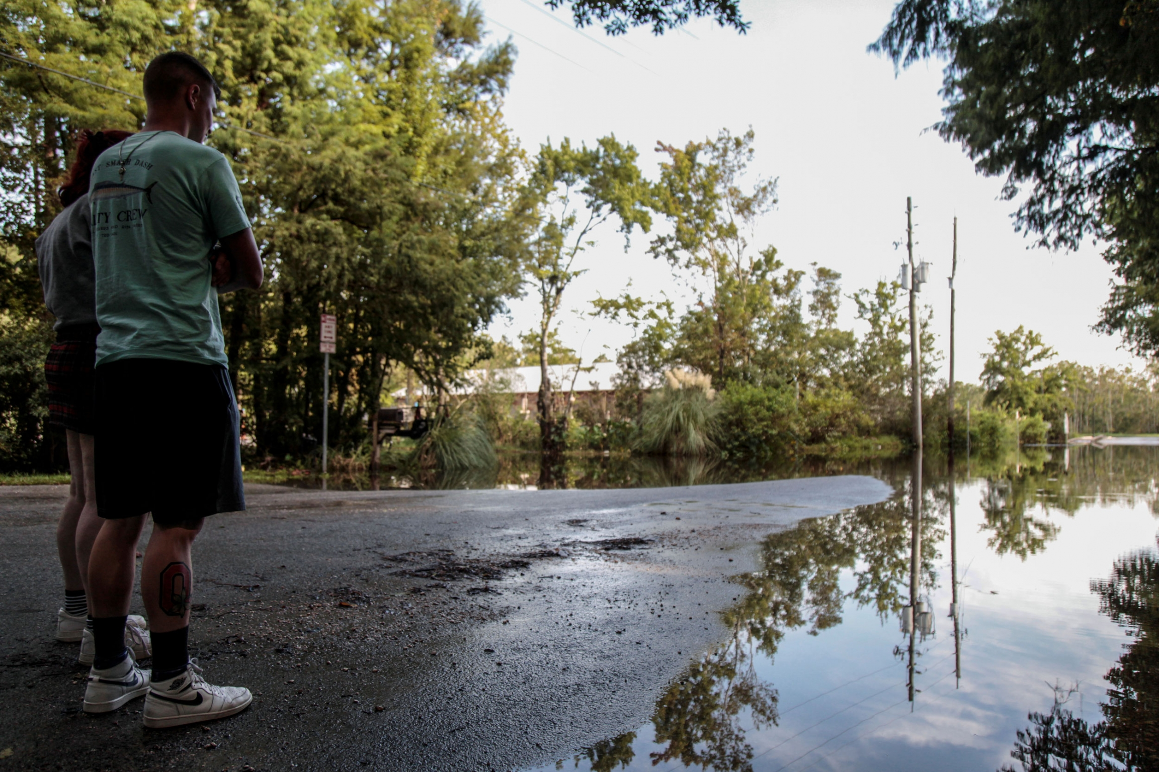Two people are shown standing on a tree-lined street partially flooded from recent storms.