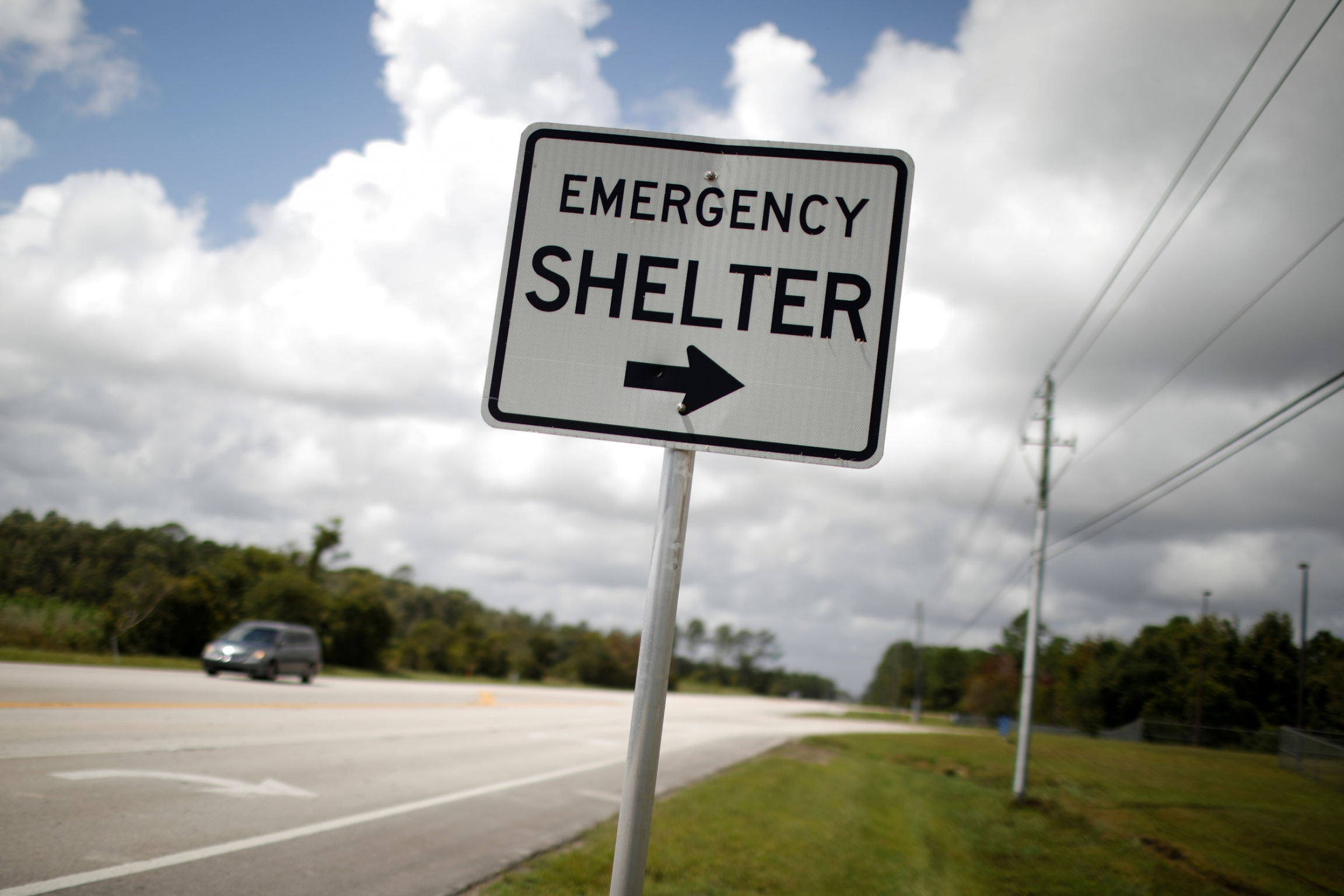 "A street sign is shown next to a road with ""Emergency Shelter"" and an arrow pointed to the right printed on it."