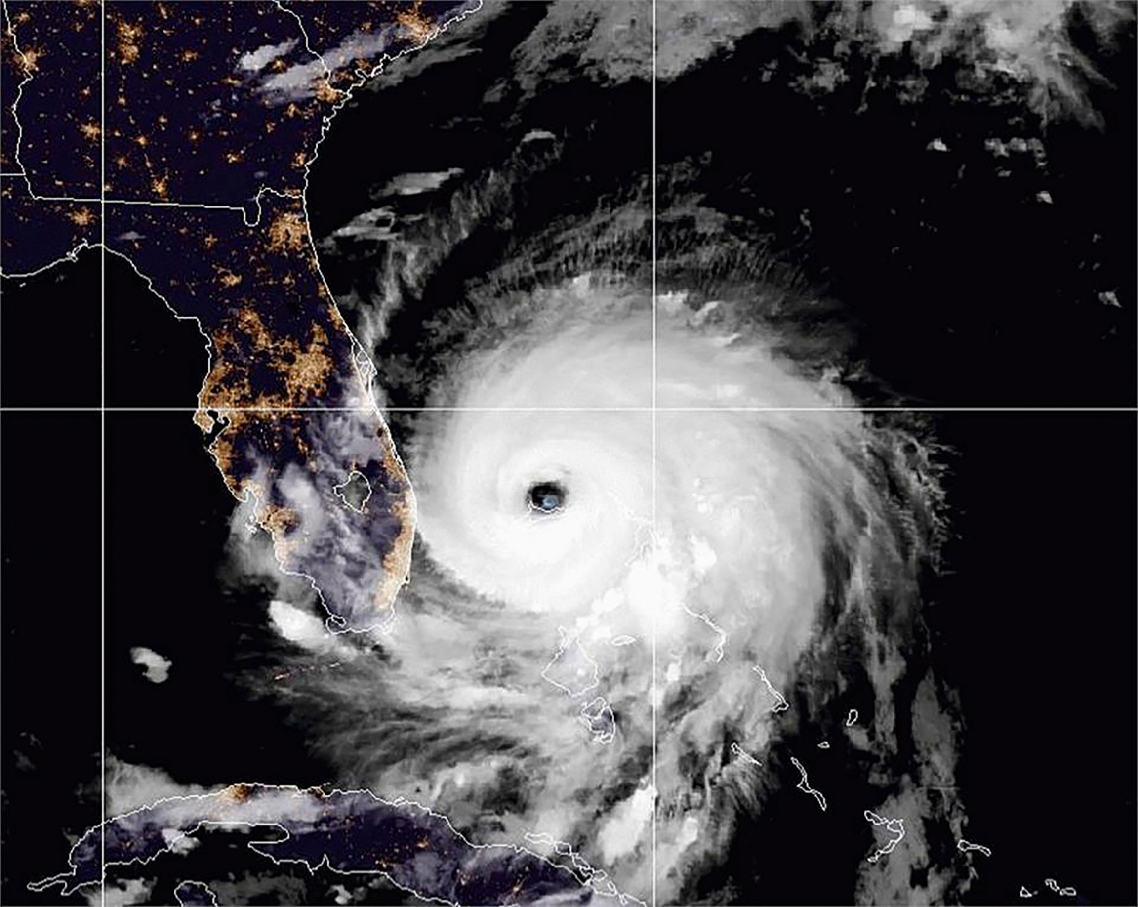 A satellite image shows the outline of Florida with the large spiral of Hurricane Dorian adjacent to the east coast.