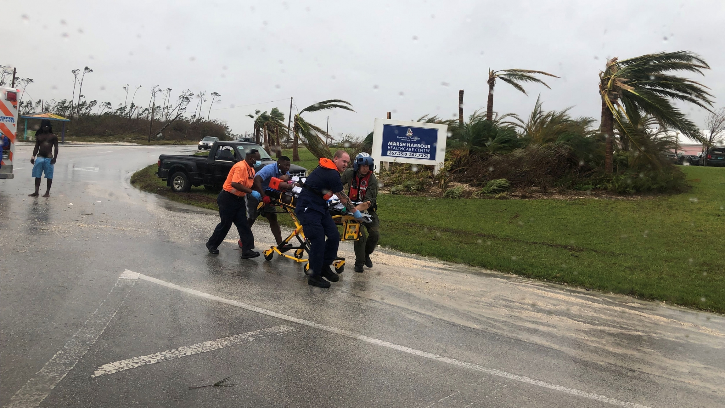 Four people run through a deserted street while pushing a guerney that's holding a patient during Hurricane Dorian.