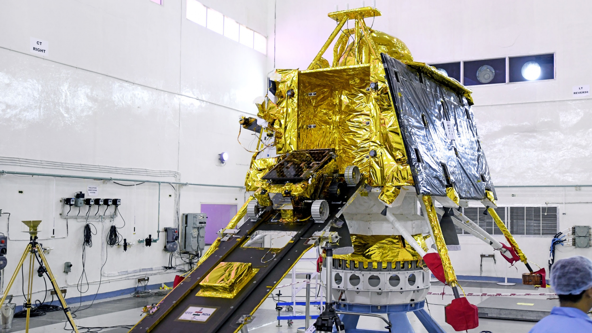 A small rover exits a large, gold spacecraft.