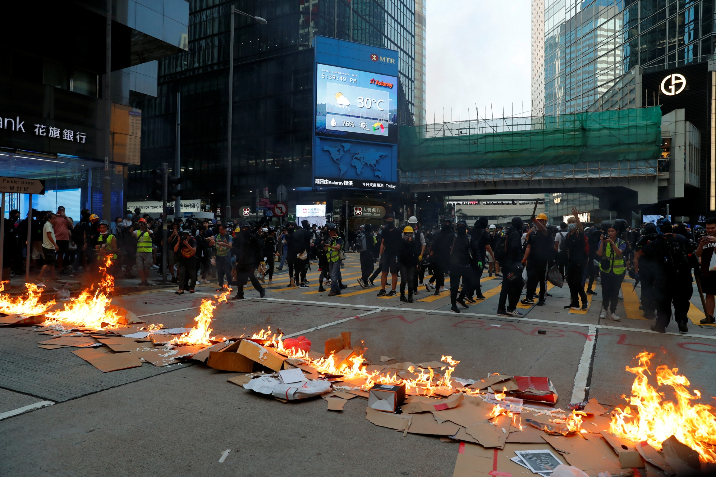 A line of fire on a road, as a crowd of people walk away