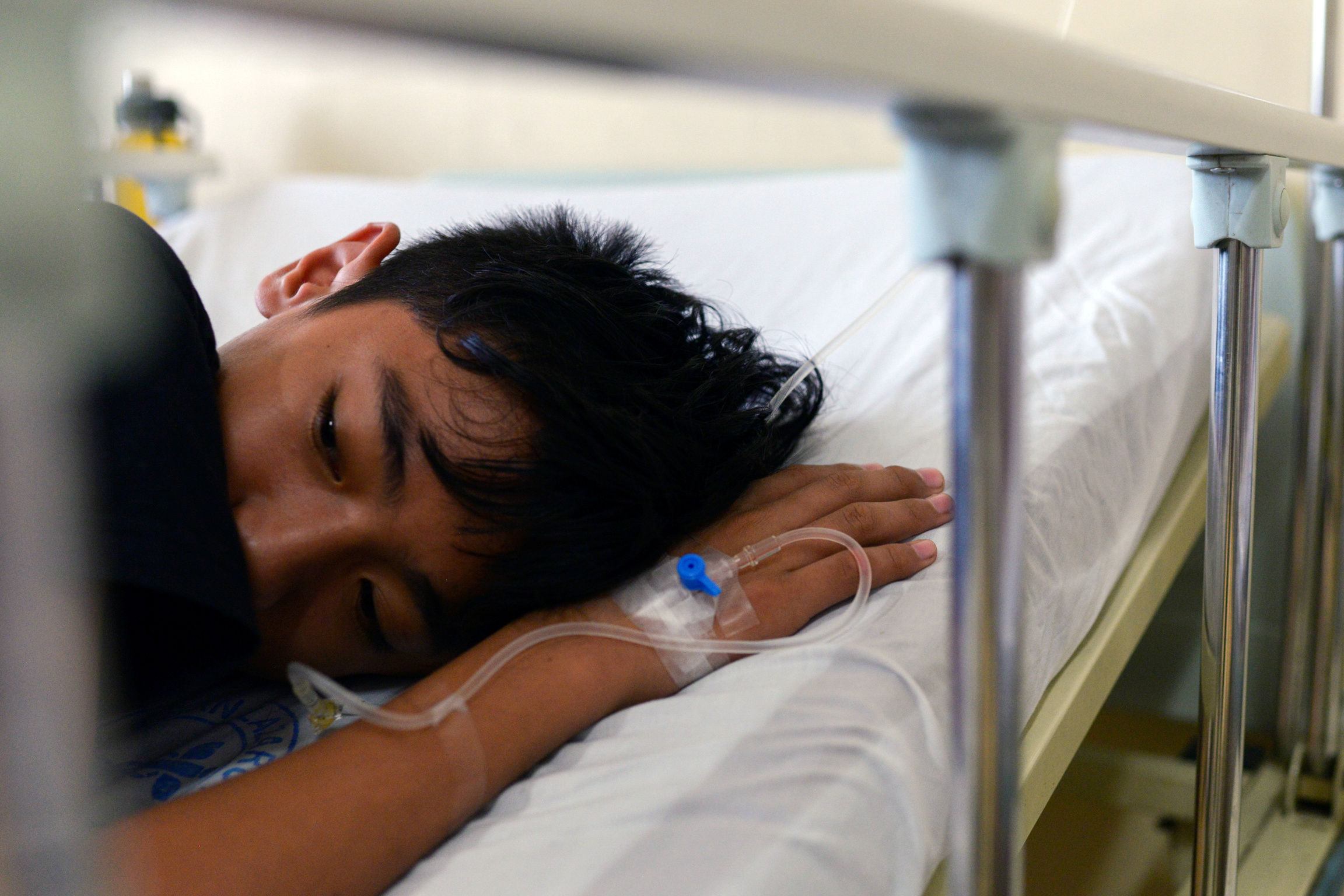 A boy lays down in a hospital bed.