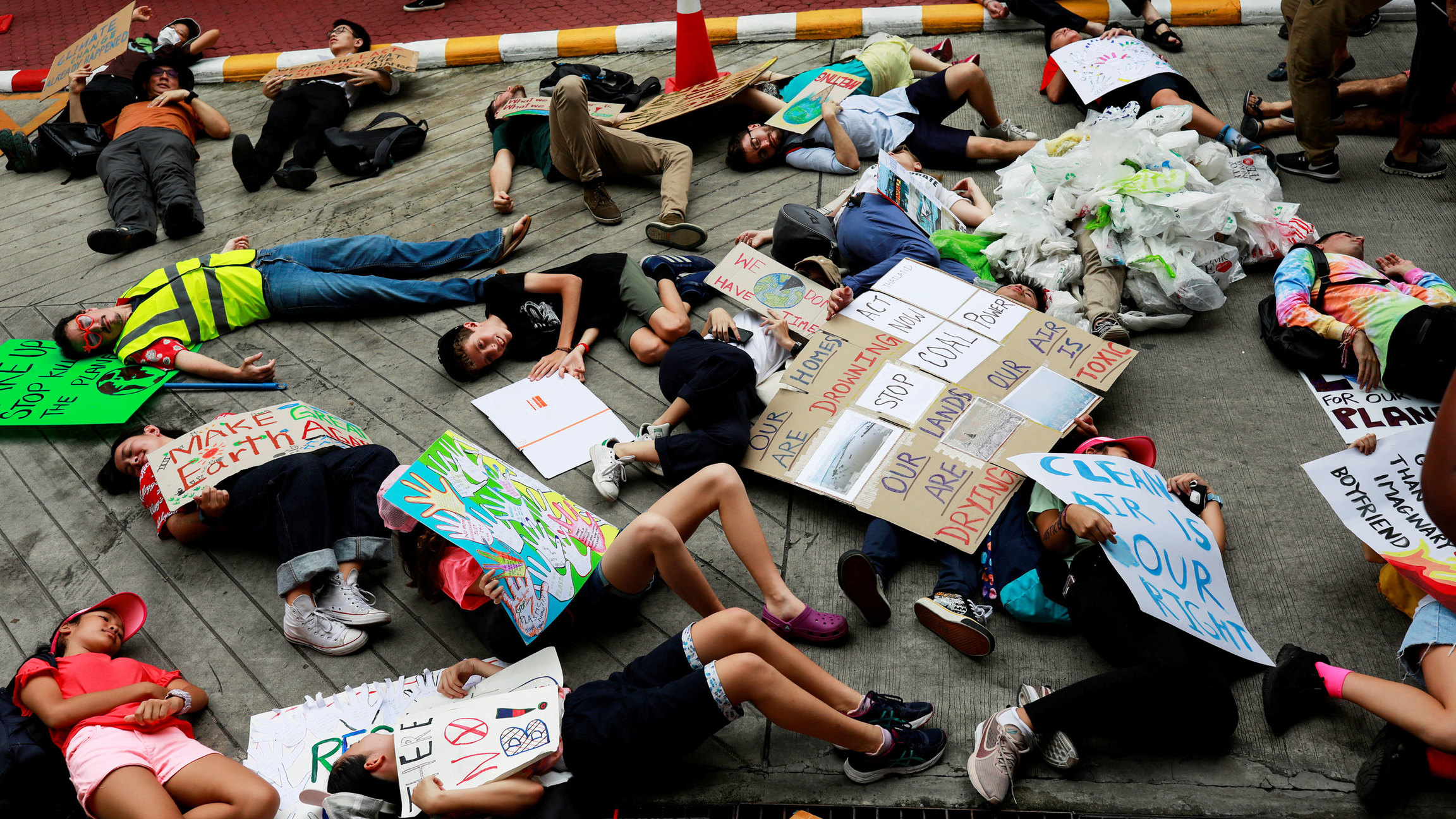 Several young people are shown laying down on the ground with placards protesting for climate change action.