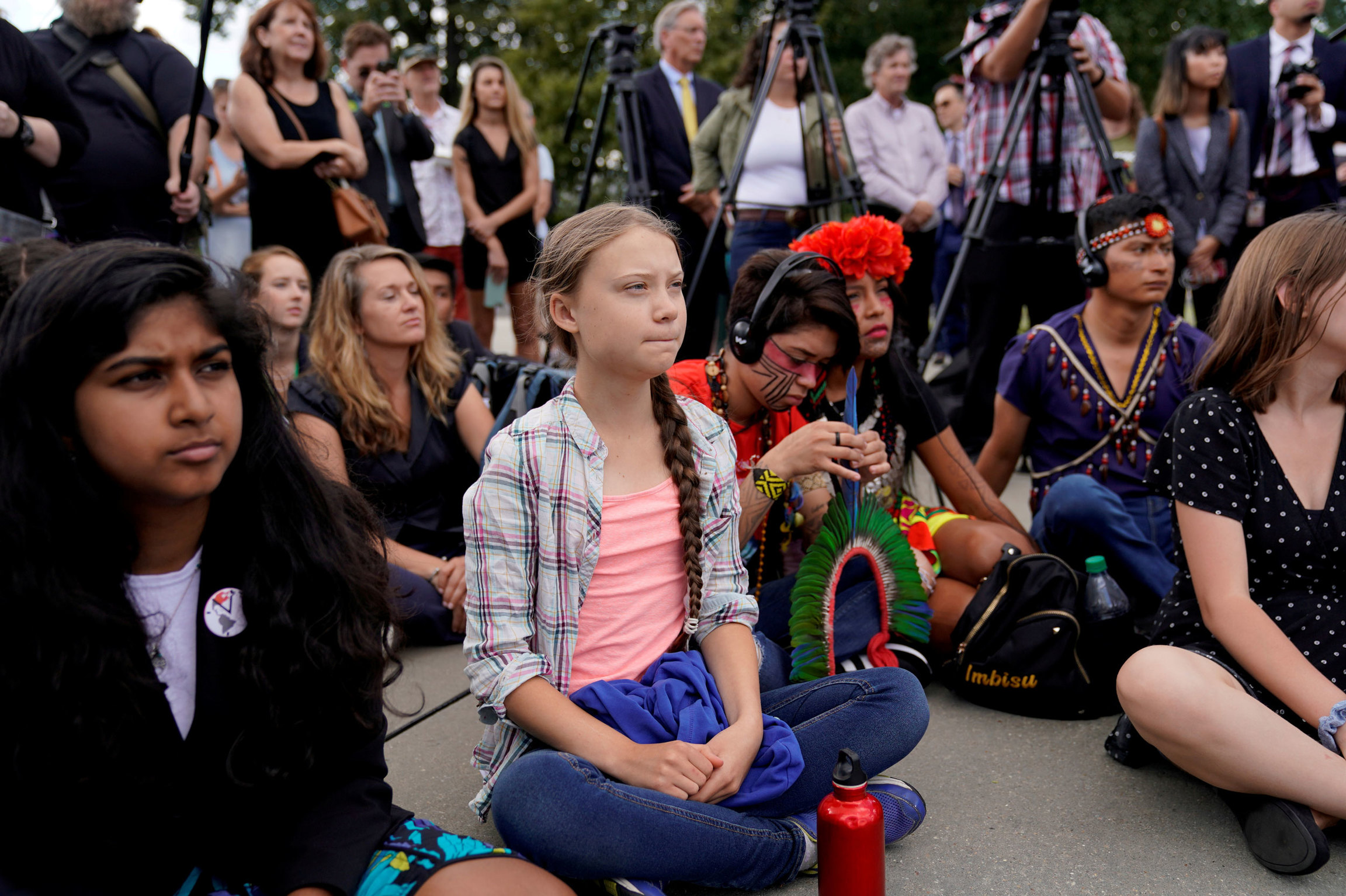 Swedish climate activist Greta Thunberg is shown sitting on the ground with her legs crossed and with a red water bottle.