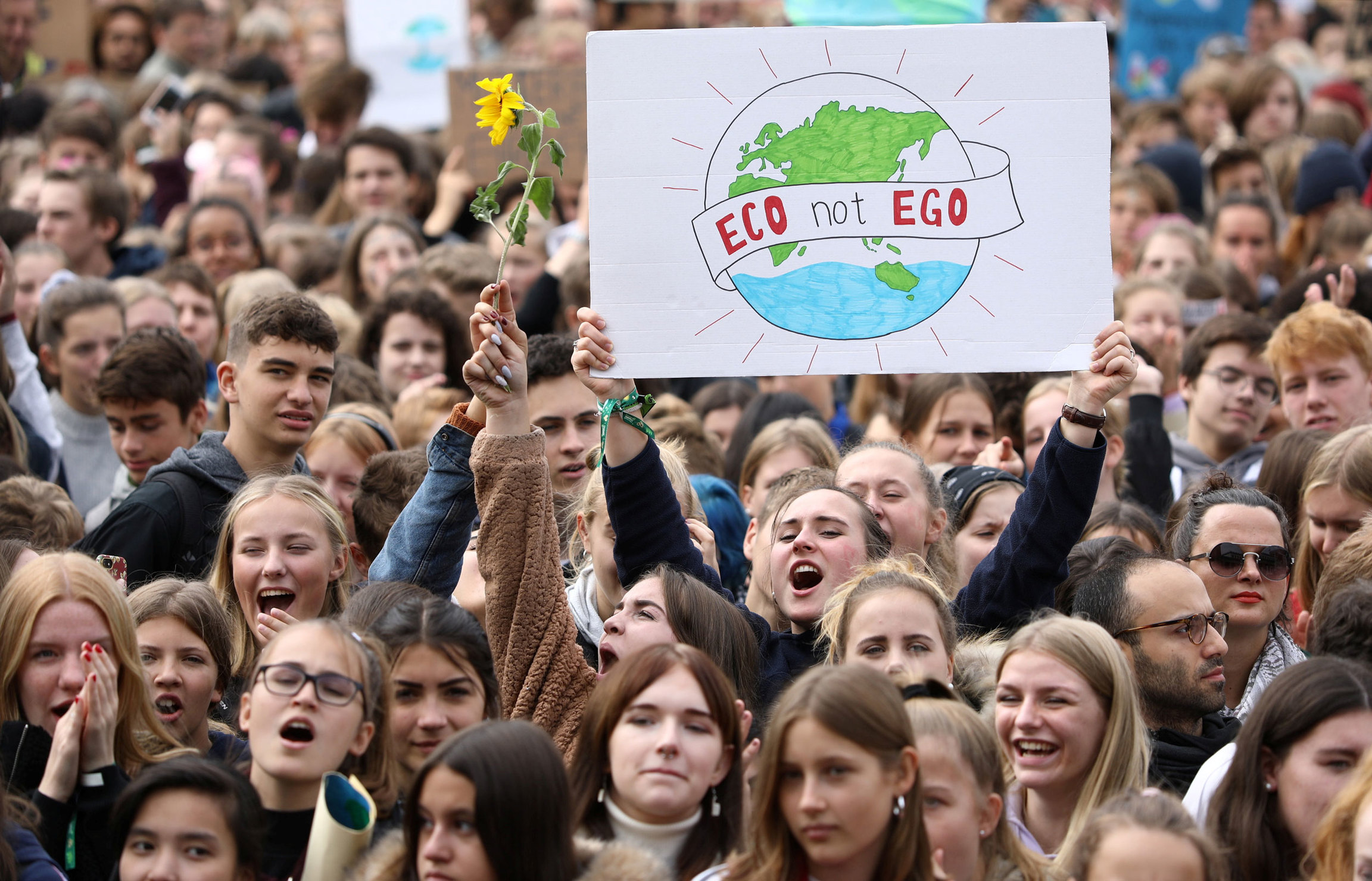"A large crowd of people are shown with one woman hollding a sign that reads, ""Eco not Ego."""