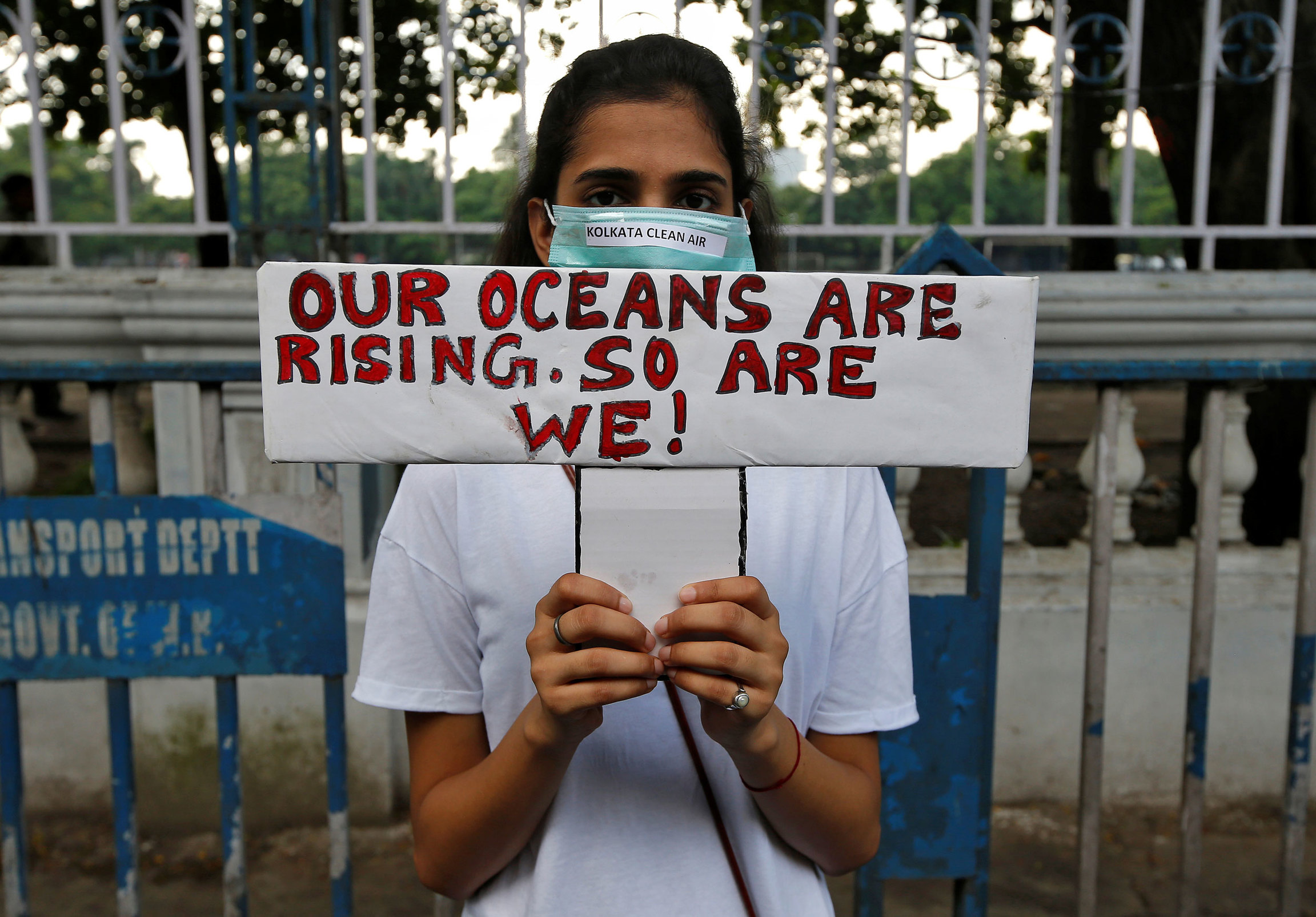 "A woman is shown standing and holding a sign that reads, ""Our oceans are rising. So are we!"""
