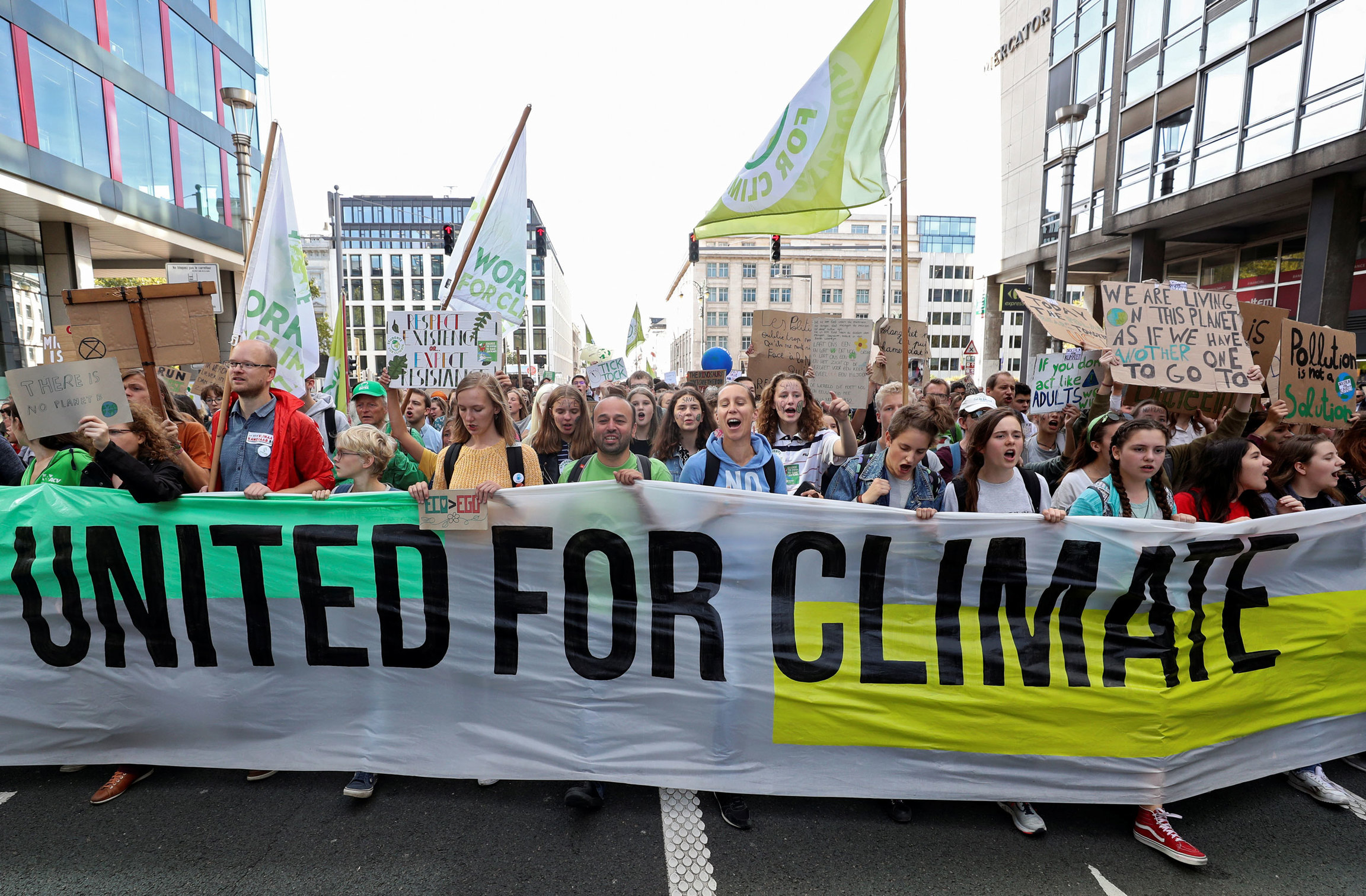 "A large group of people are shown in the street with a long banner that reads, ""United for Climate."""