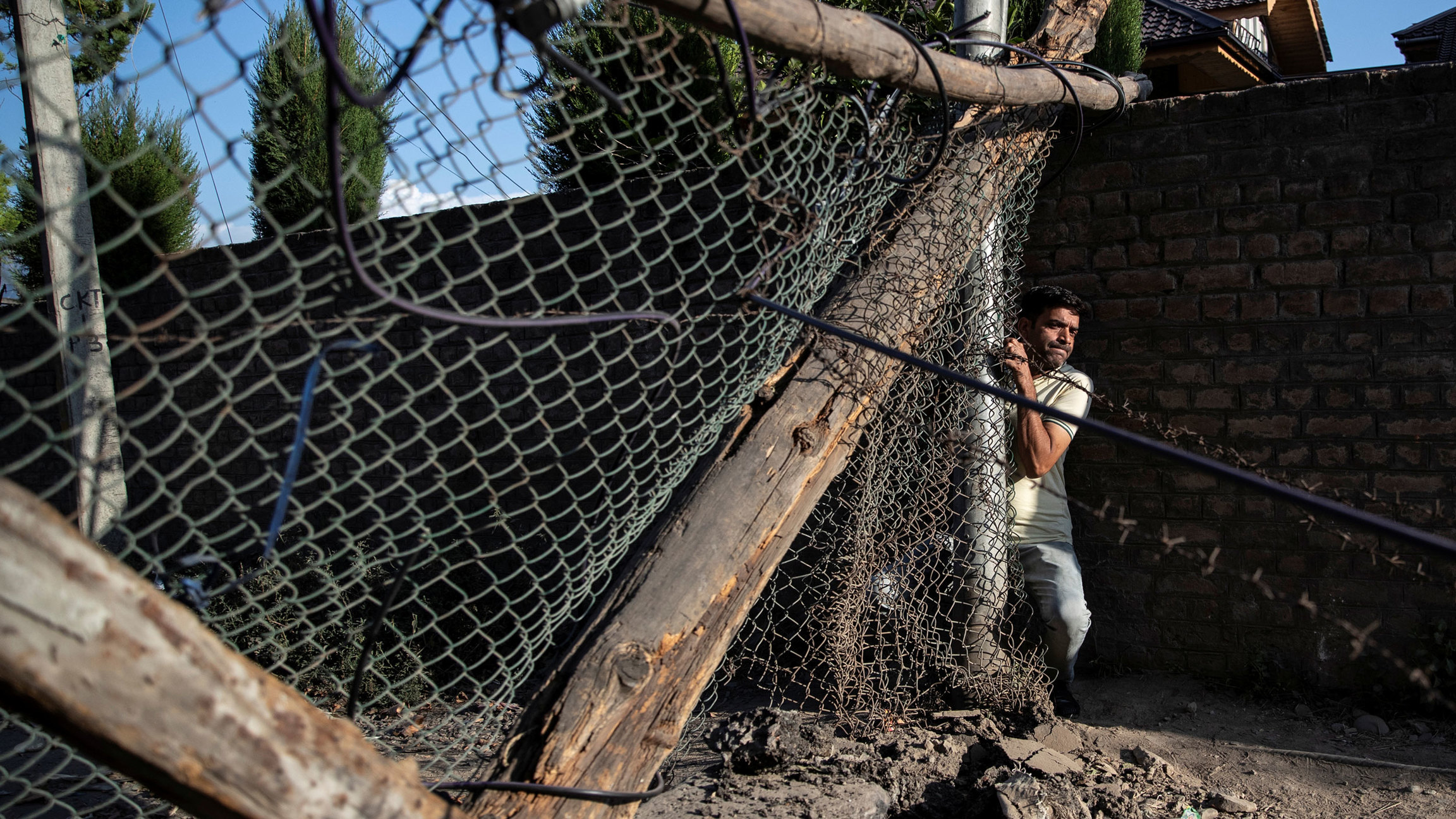 A Kashmiri man is shown squeezing his body through a chain link and wooden barricade.