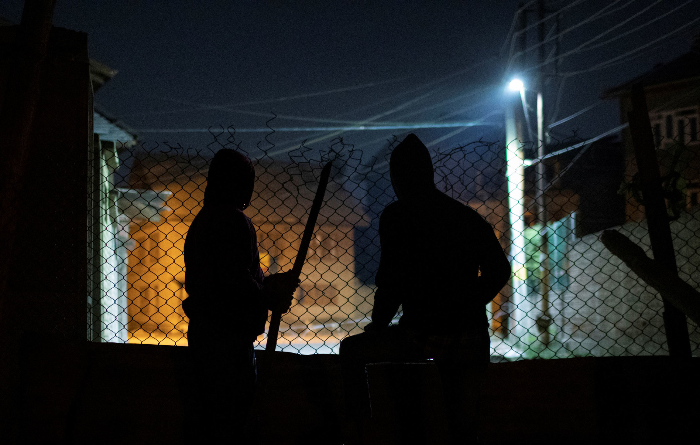 Two men are shown in shadow with a chain link fence in front of them with only the light of a streetlamp.