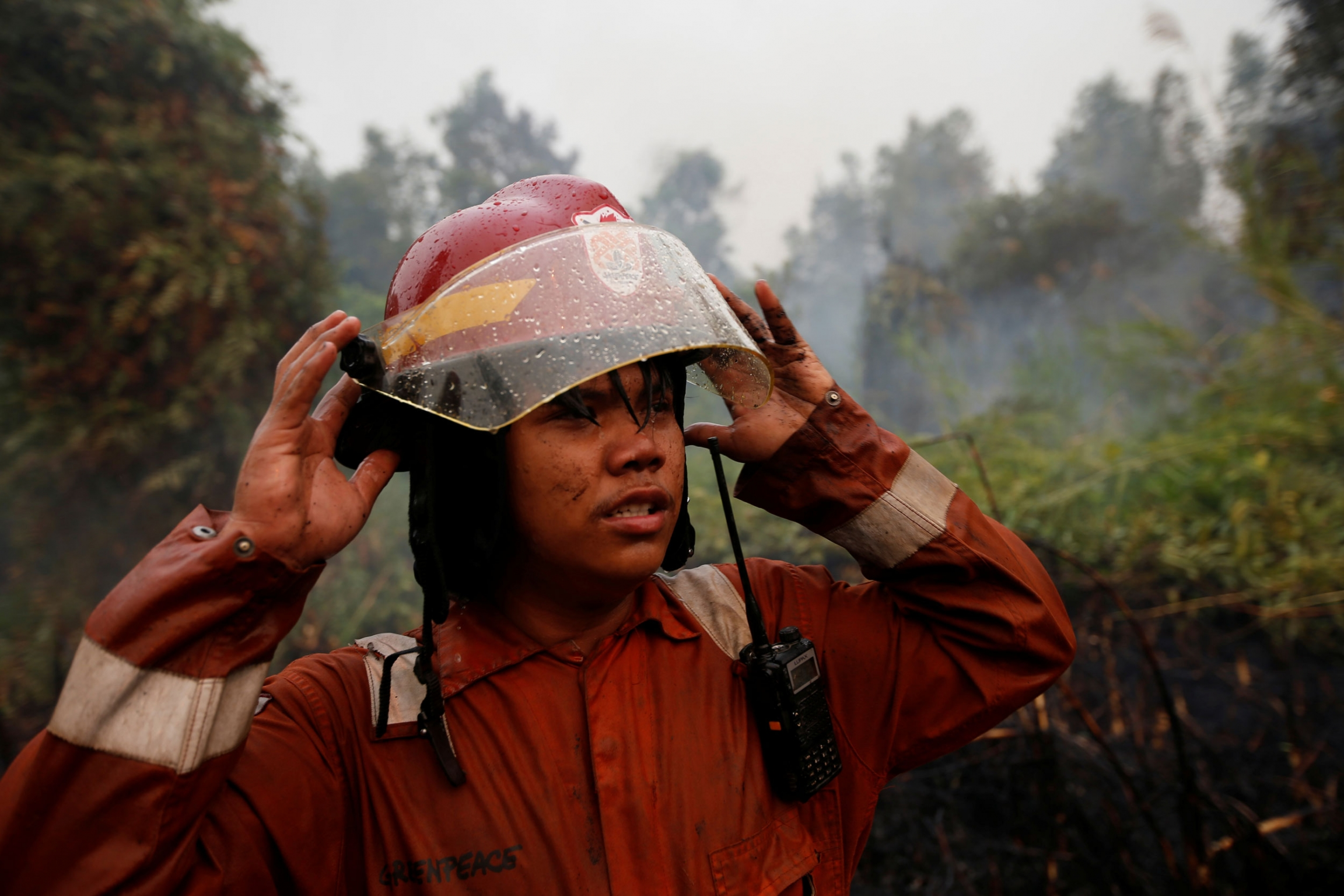 A man is shown with his hands rised to the brim of his fire helmet.