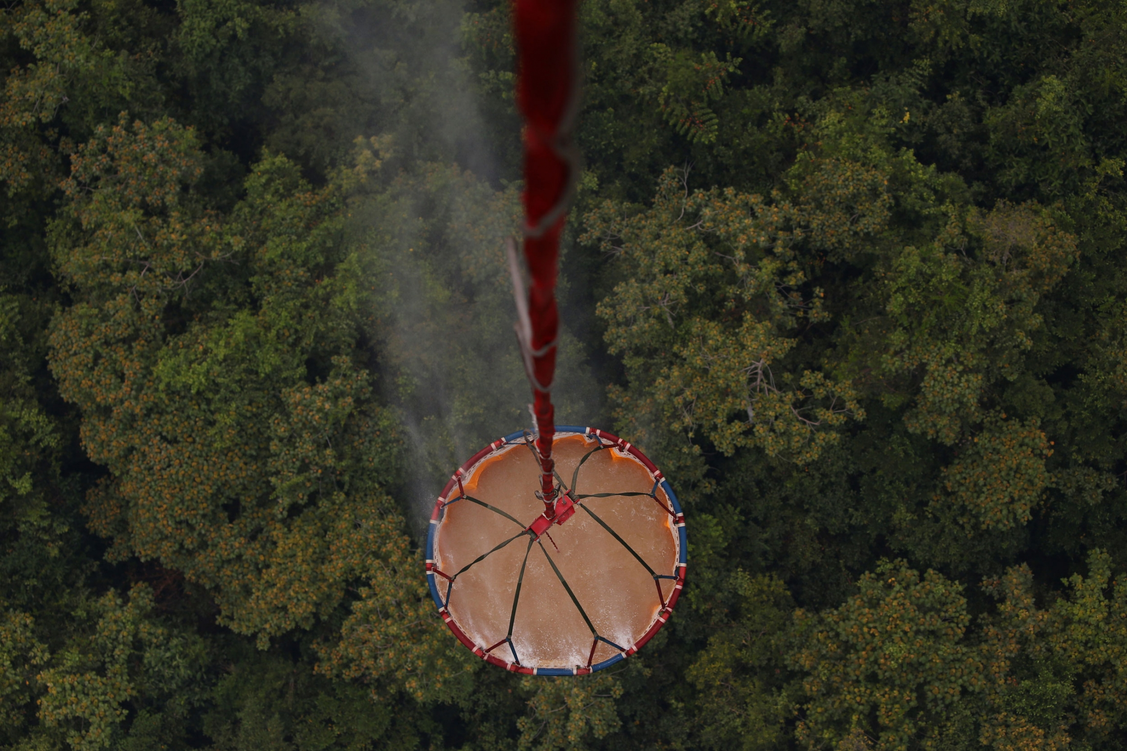 An ariel view is shown looking down at a large container of water with a forest down below.