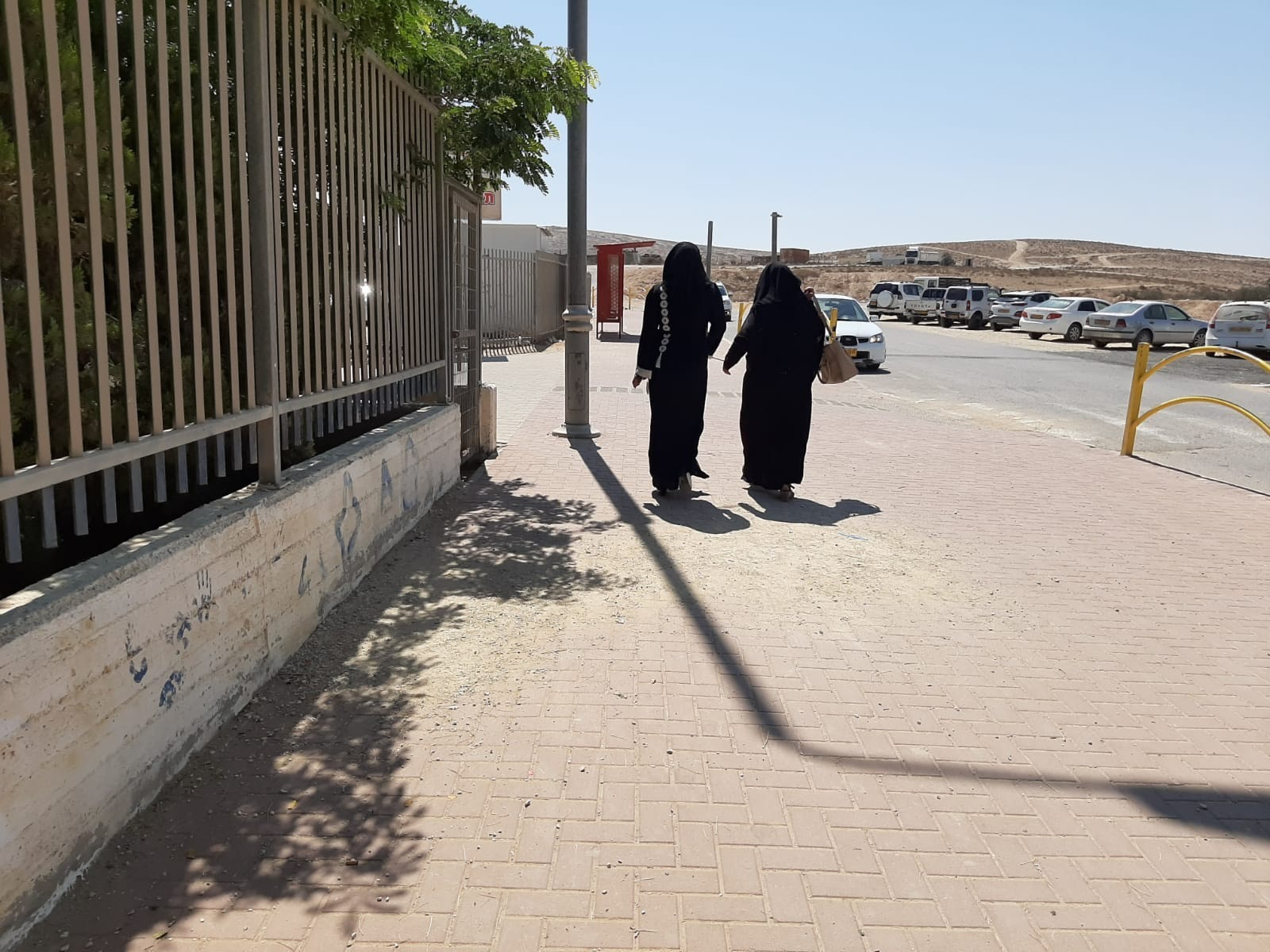 Two women in black walk away from voting station