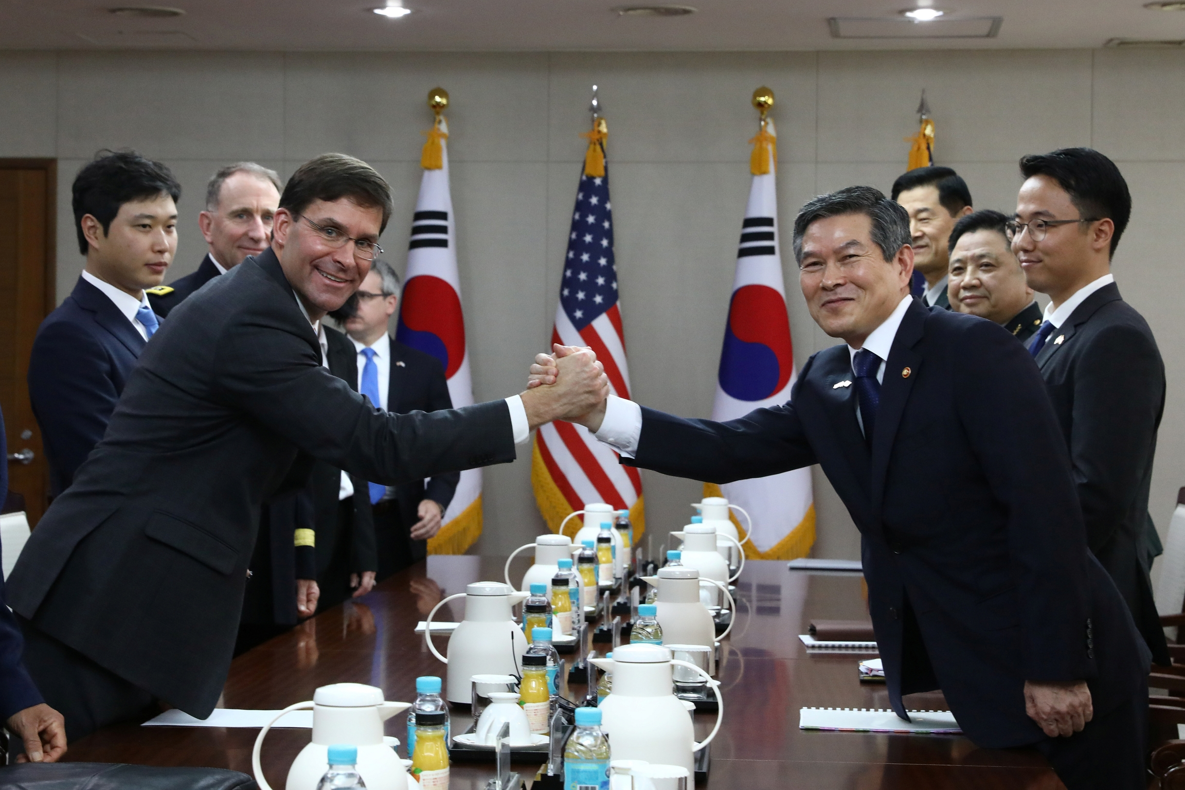 President Moon Jae-in shakes hands with US military wearing uniforms across a table