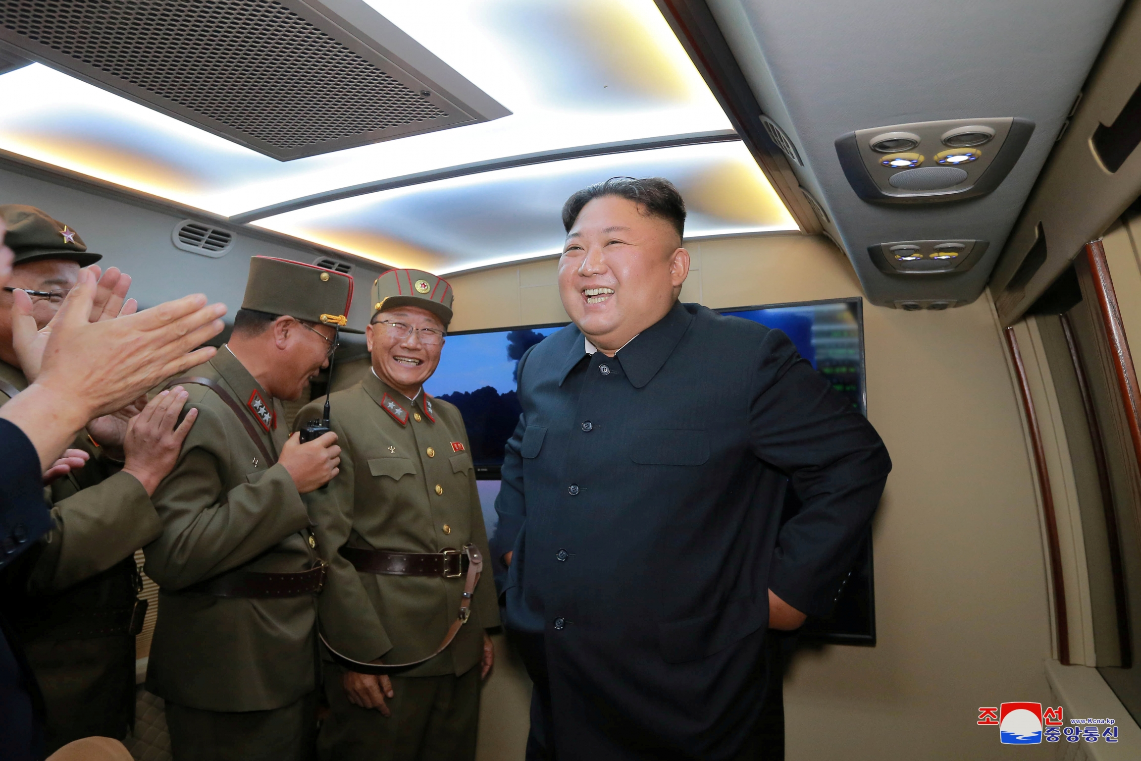 Kim Jong-un smiles in gray suit as he talks with men in green military uniforms