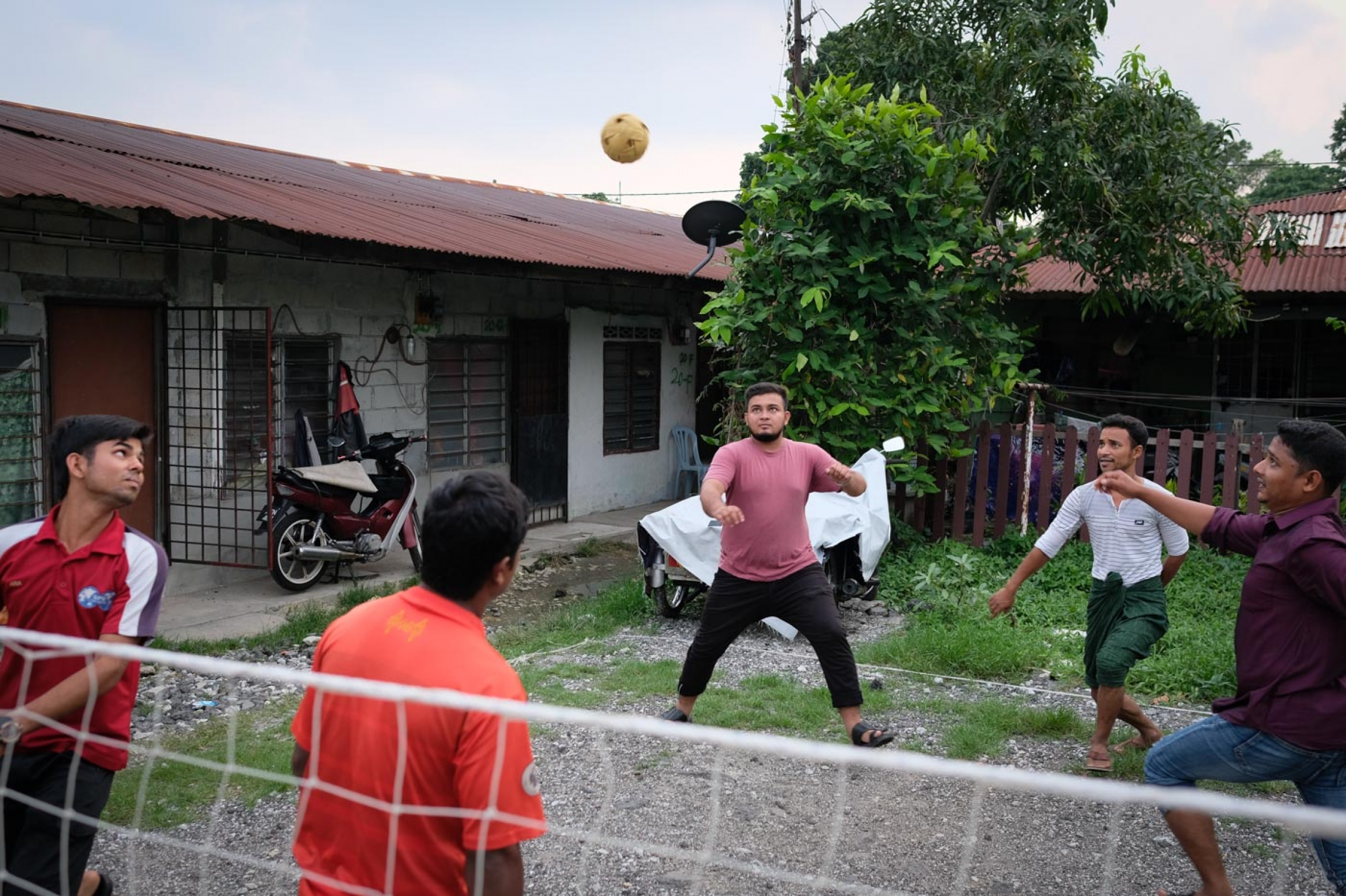 A group of young men play kick volleyball with a net