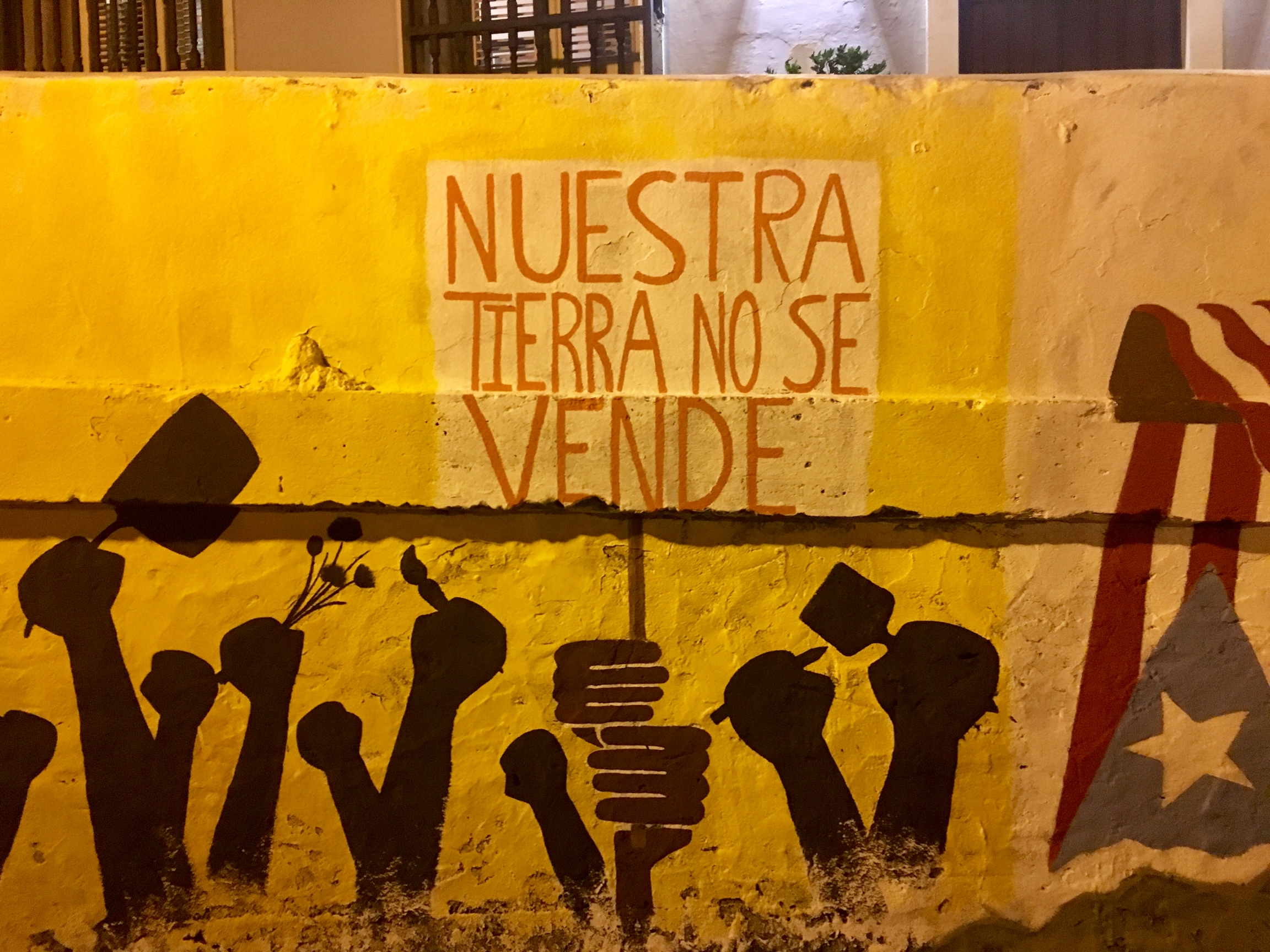 Our land is not for sale painted on a wall in Spanish with yellow paint