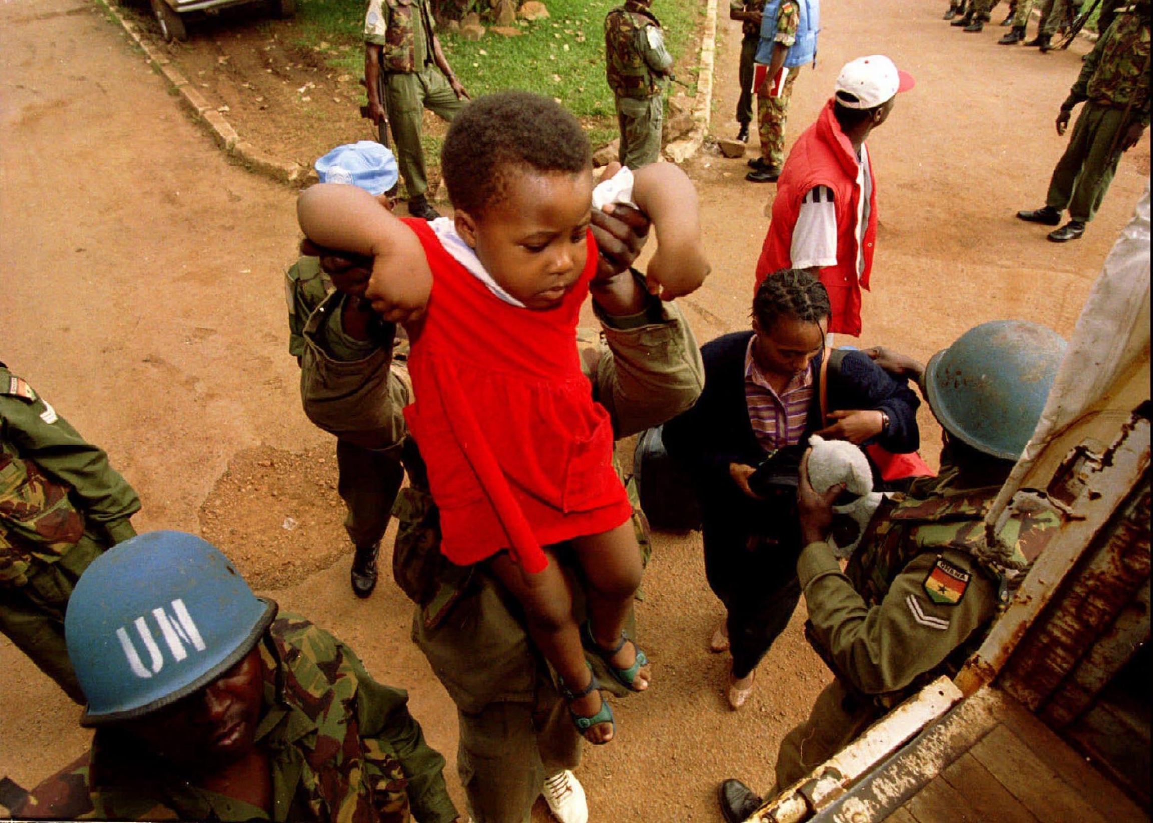UN peacekeepers hold up a child.