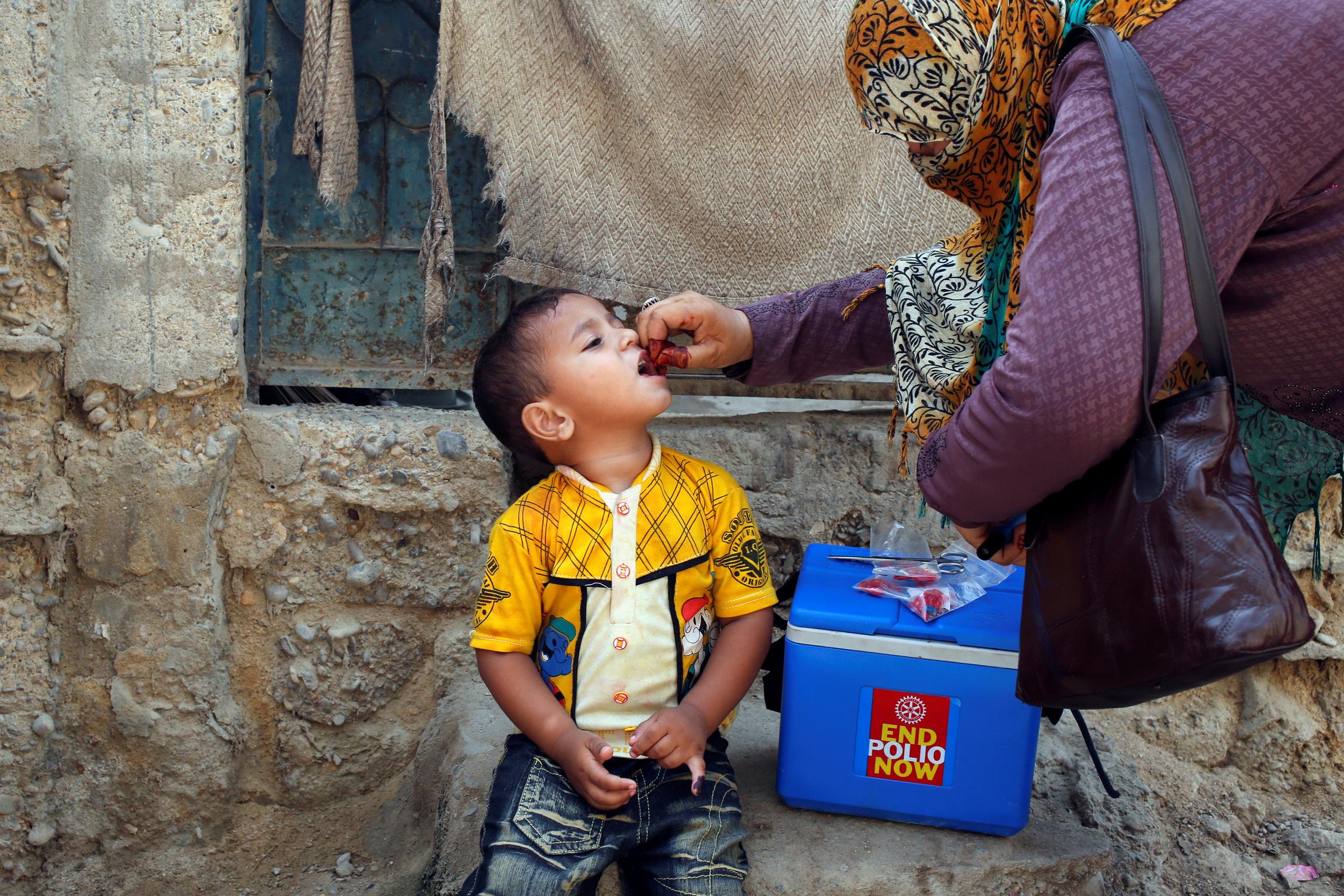 A woman gives a boy an oral polio vaccine.