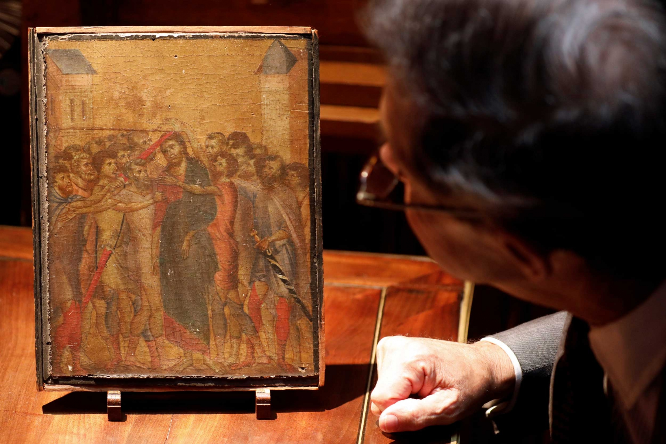 A man looks closely at a small religious image showing Christ surrounded by other men