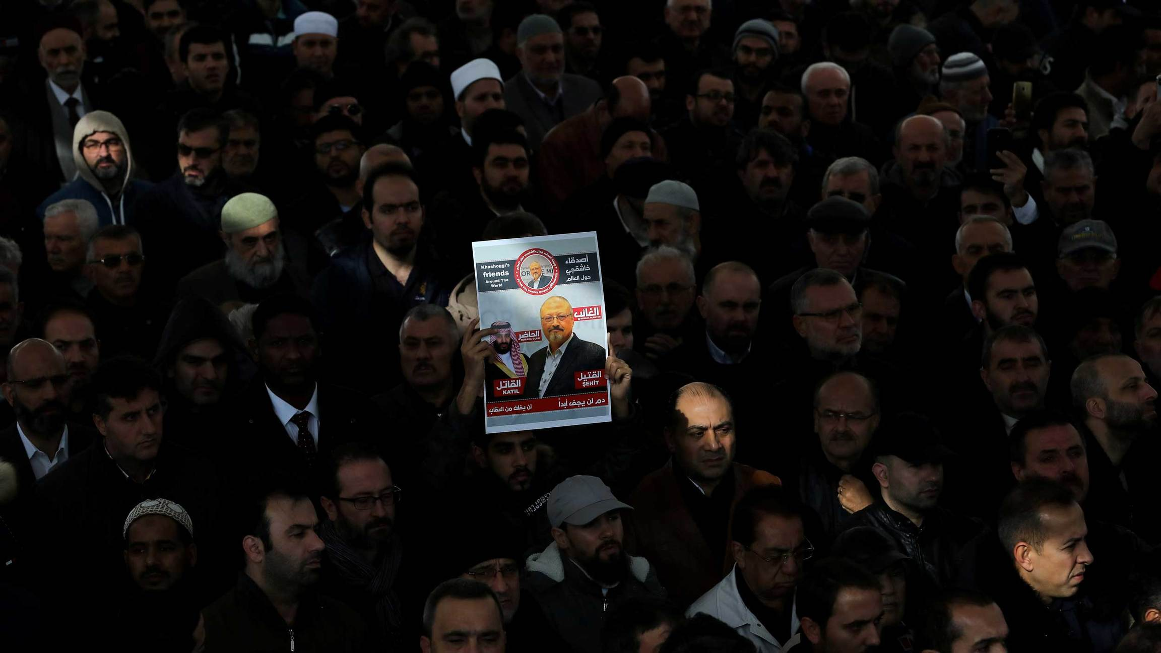 Dozens of people are praying and one person holds up a sign with Jamal Khashoggi's image on it