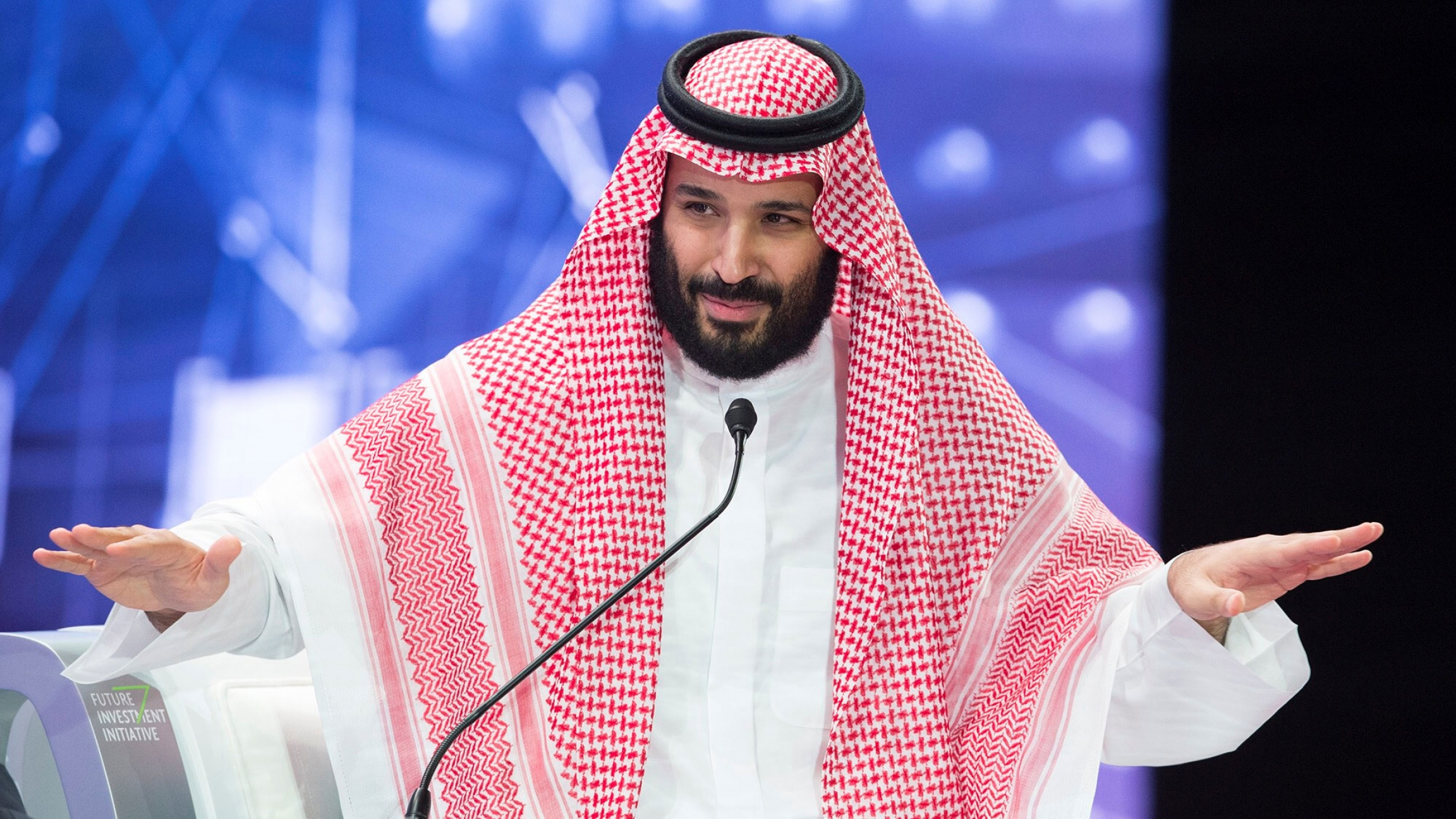 Crown Prince Mohammad bin Salman is picture with his hands outstretched, talking at a microphone