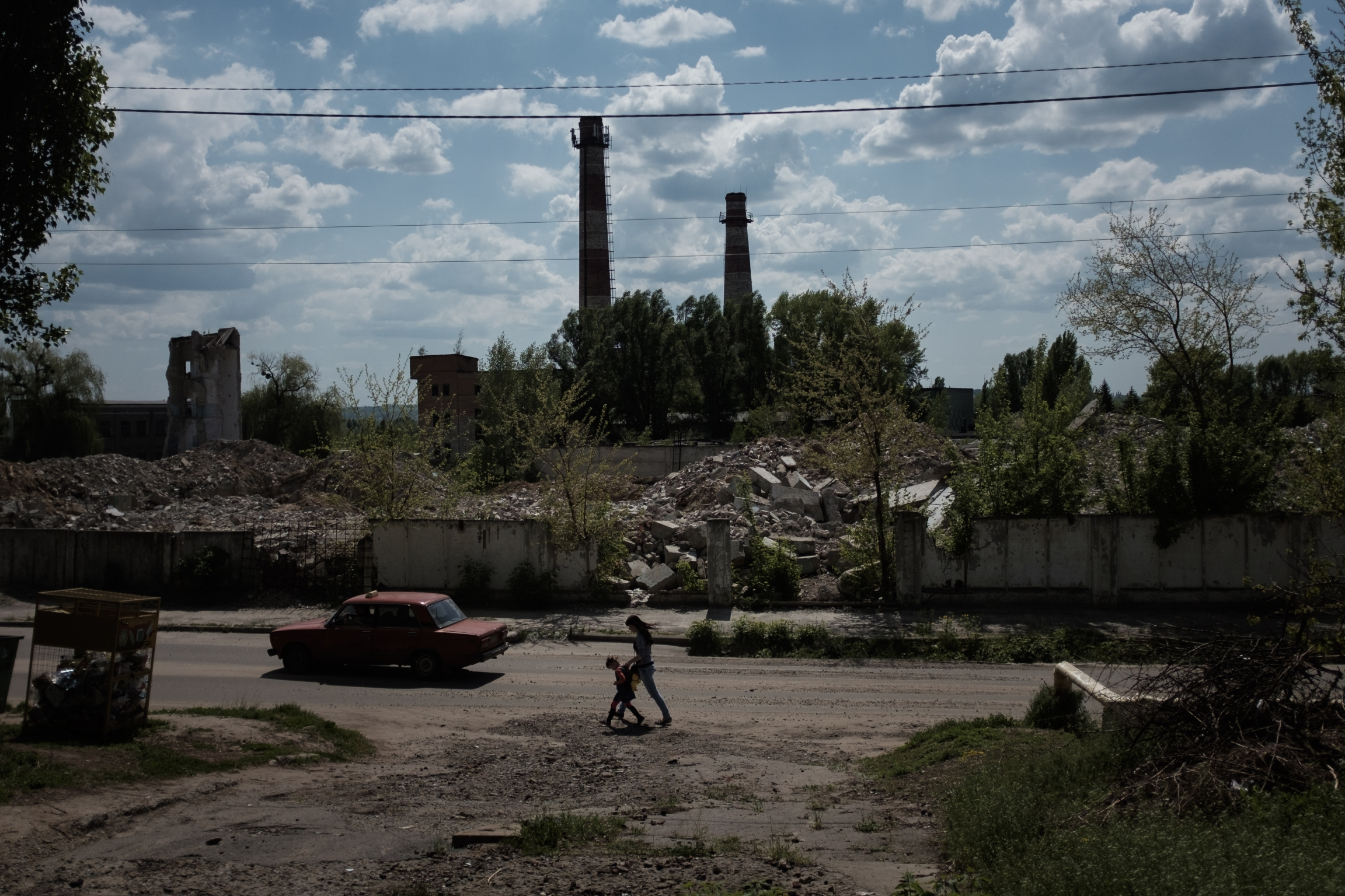 A woman and a child walk amid factory ruins