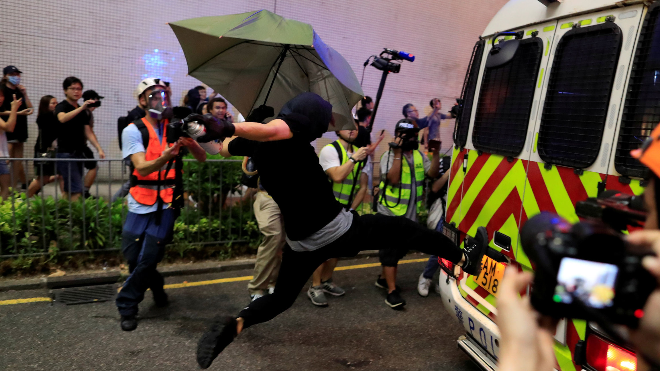 A protester is shown in mid-air kicking a police vehicle with their face fully covered in a mask.