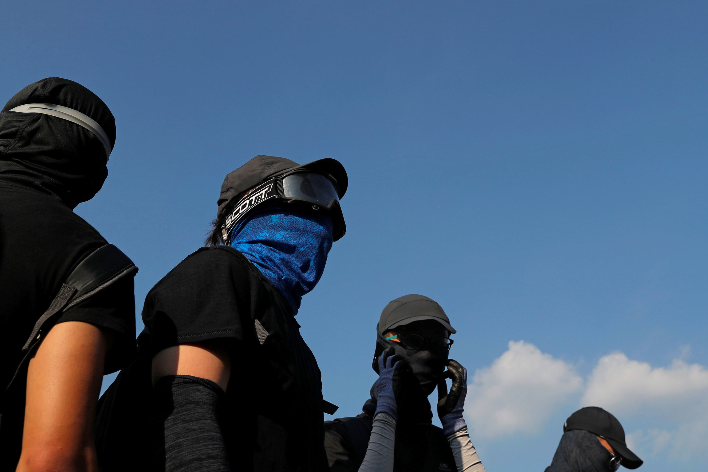 Several people are shown wearing face masks and goggles with a blue sky in the background.