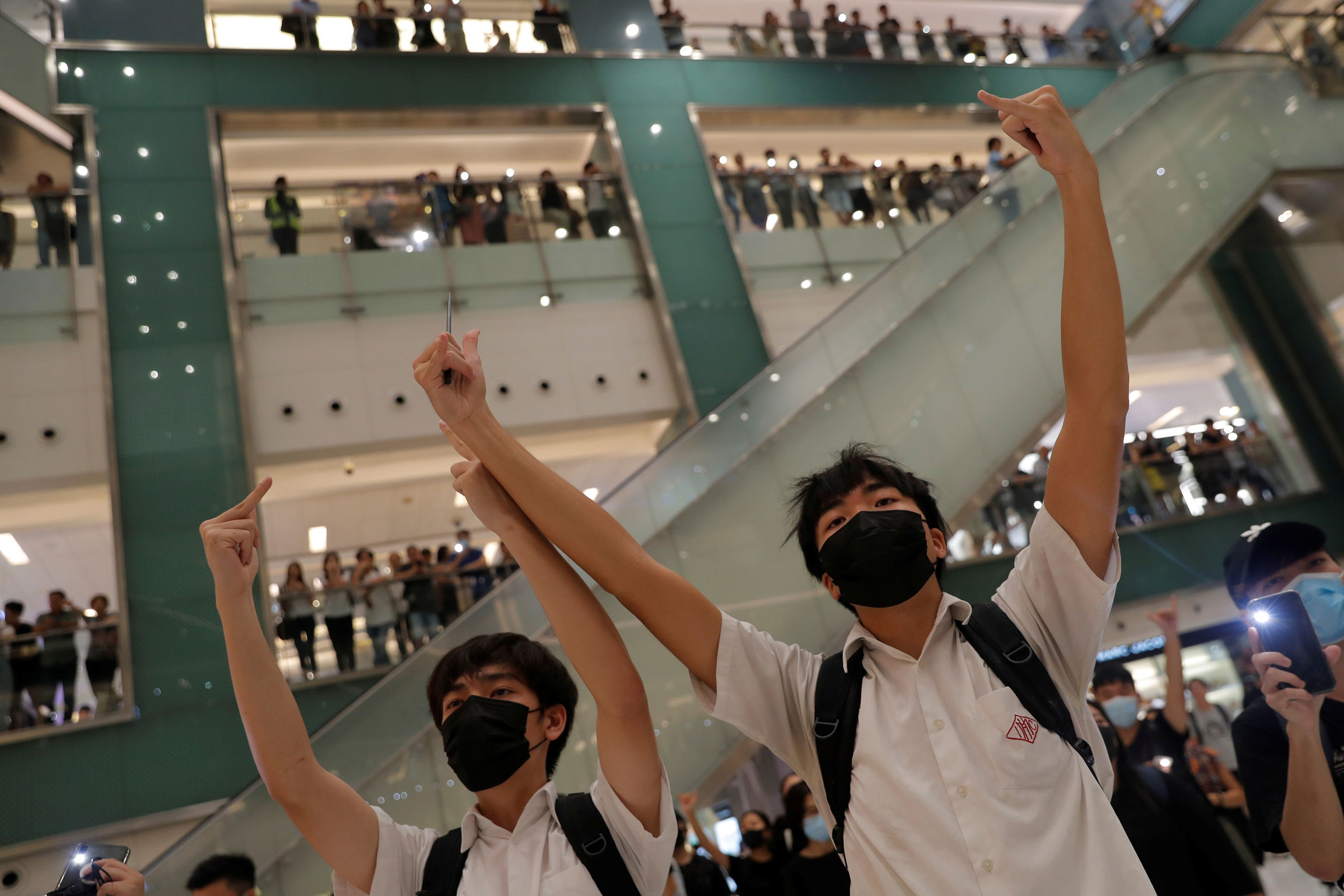 Two men are shown wearing back packs and black masks with their arms raised in the air gesturing.