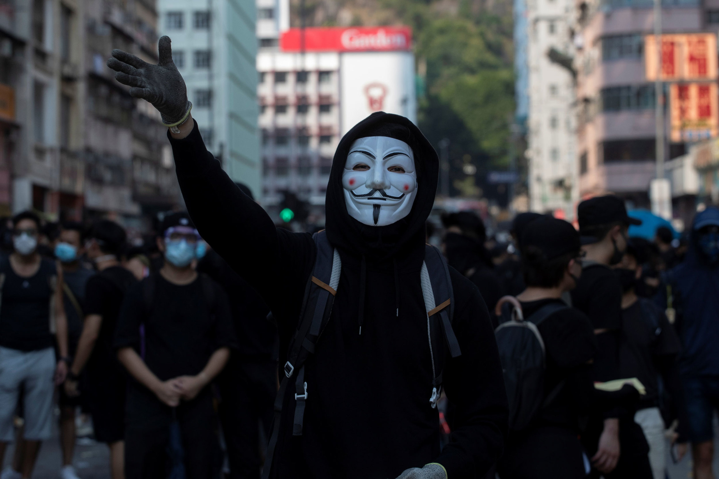 A person is shown center frame wearing a Guy Fawkes maks with their right raised hand in the air.