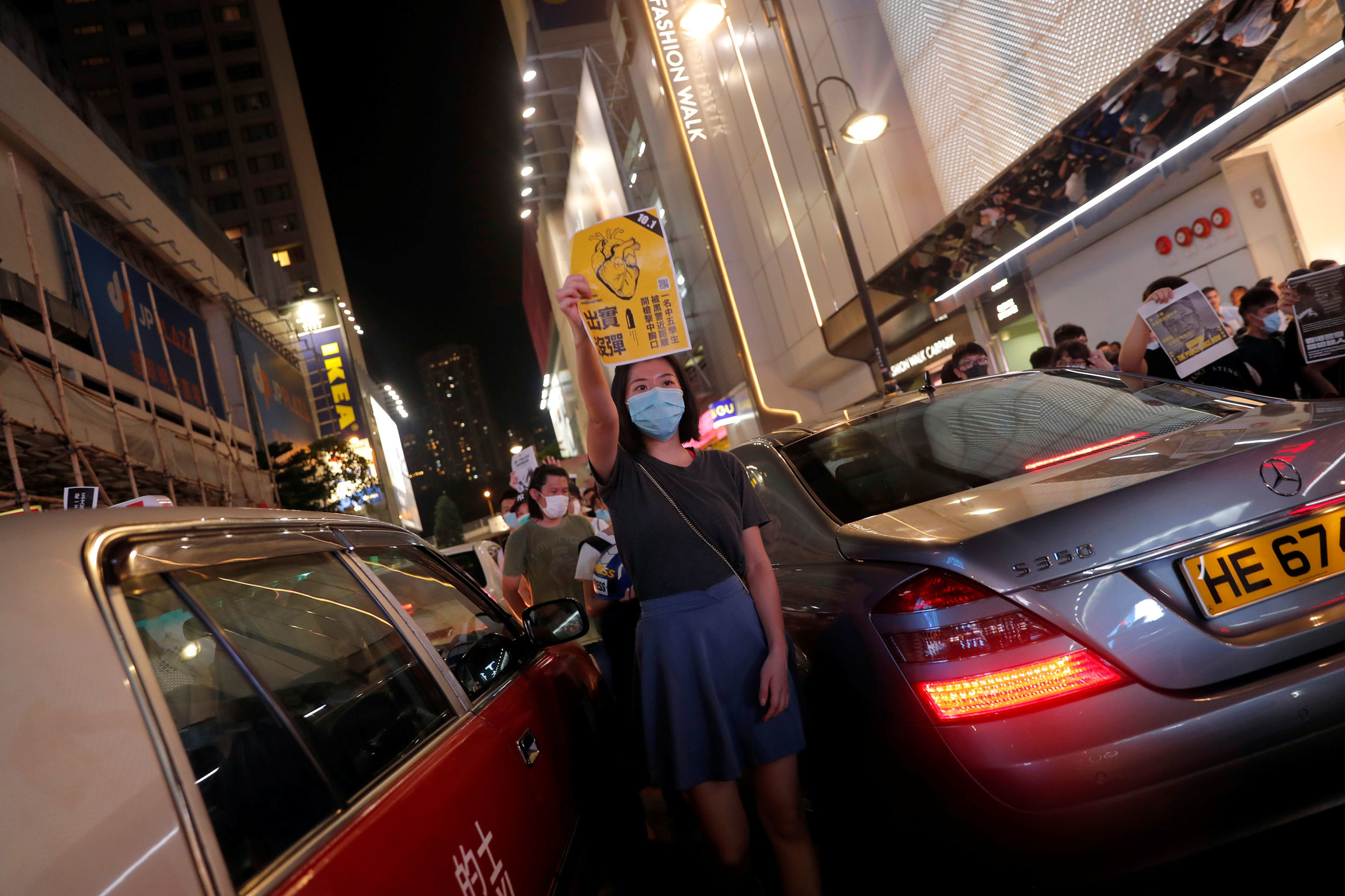 A woman is shown wearing a hospital mask and standing inbetween two cars.