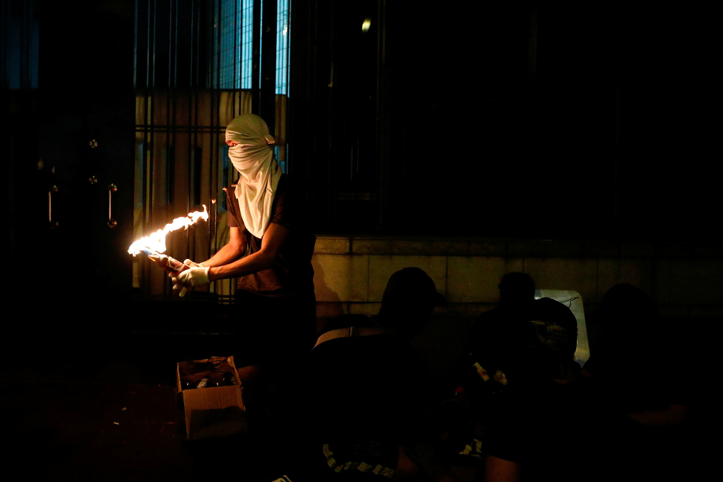 An anti-government protester is shown holding a Molotov cocktail set ablaze and wearing white mask covering his face and head.