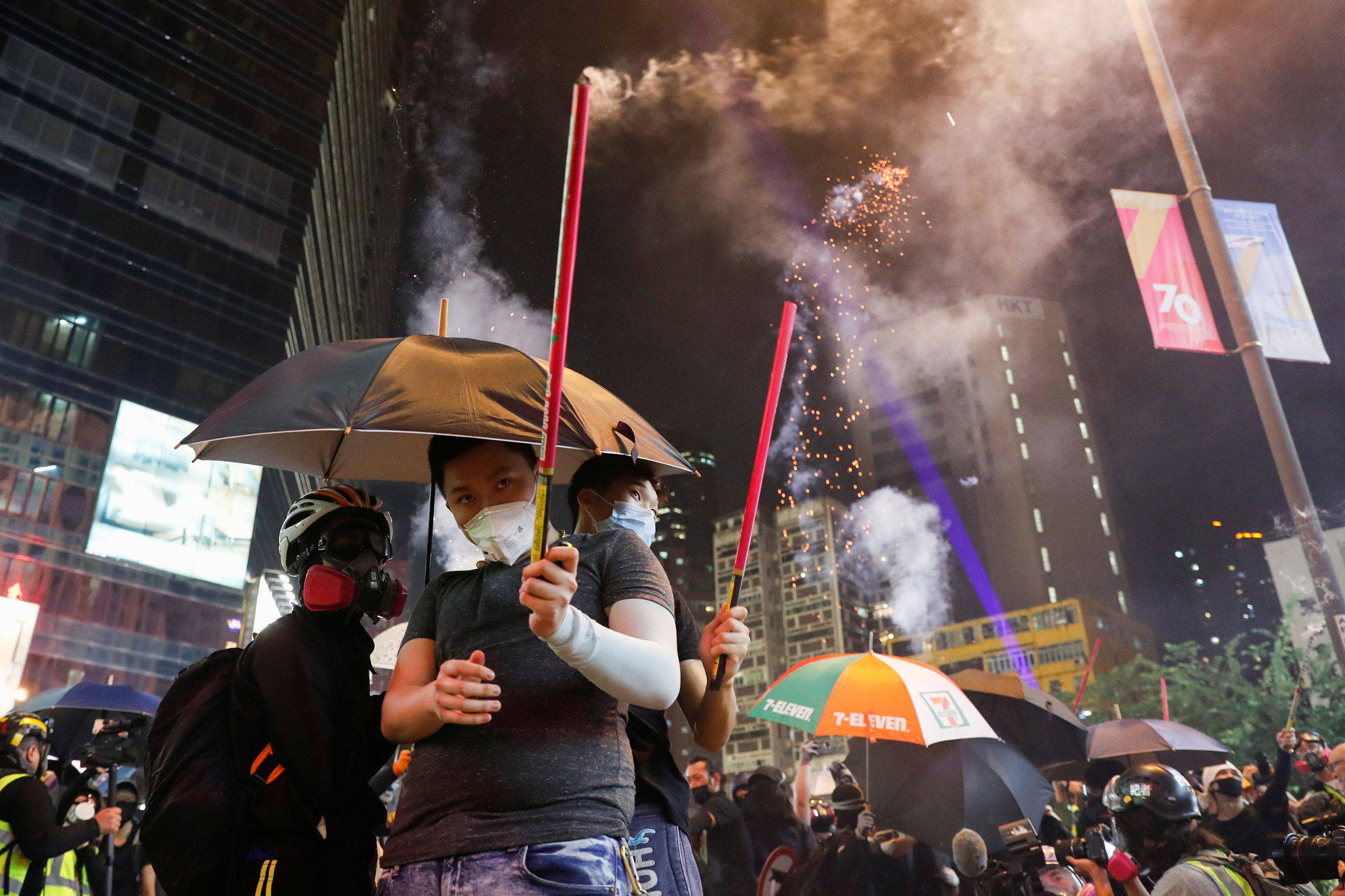 A group of protesters are shown with umbrellas and holding fireworks.