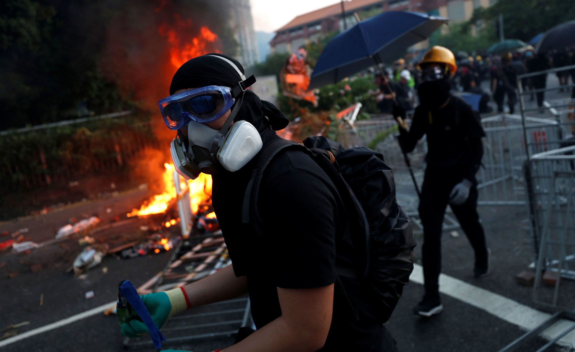 A protester is shown wearing goggles and a gas mask walking past a blazing fire.