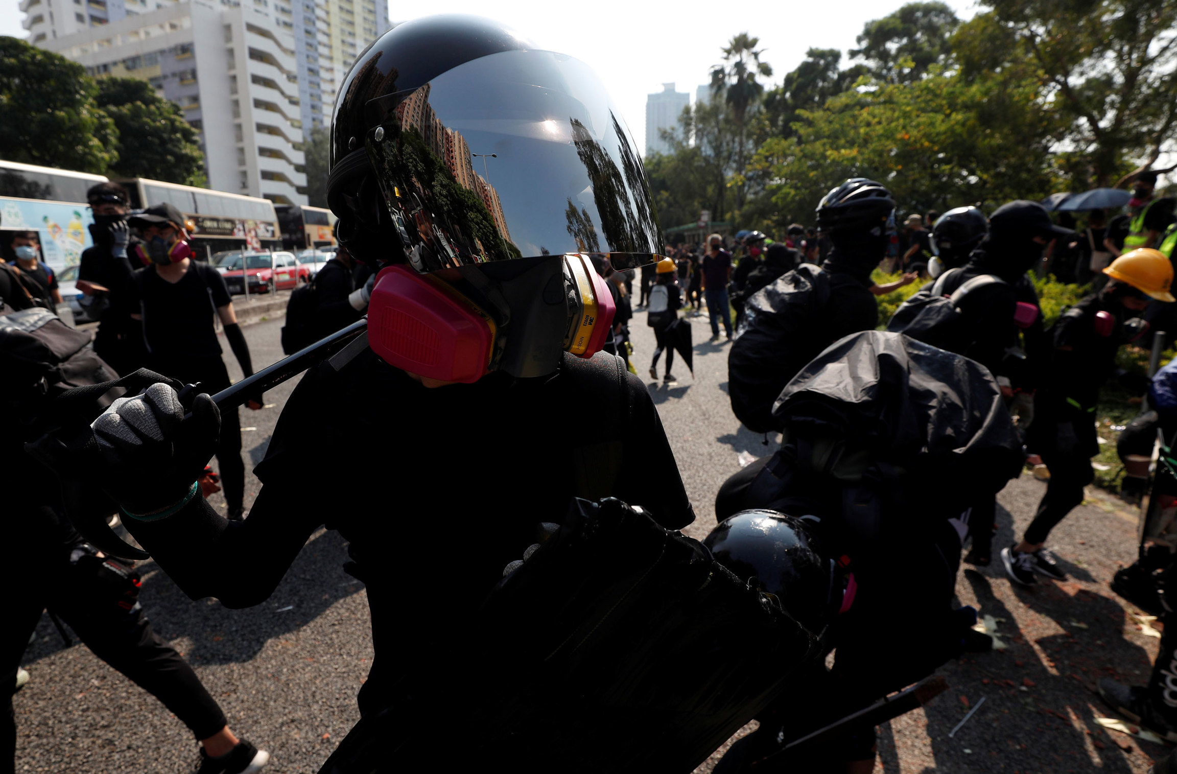 A protester is shown wearing a helmet with a reflective face shield and a pink gas mask.