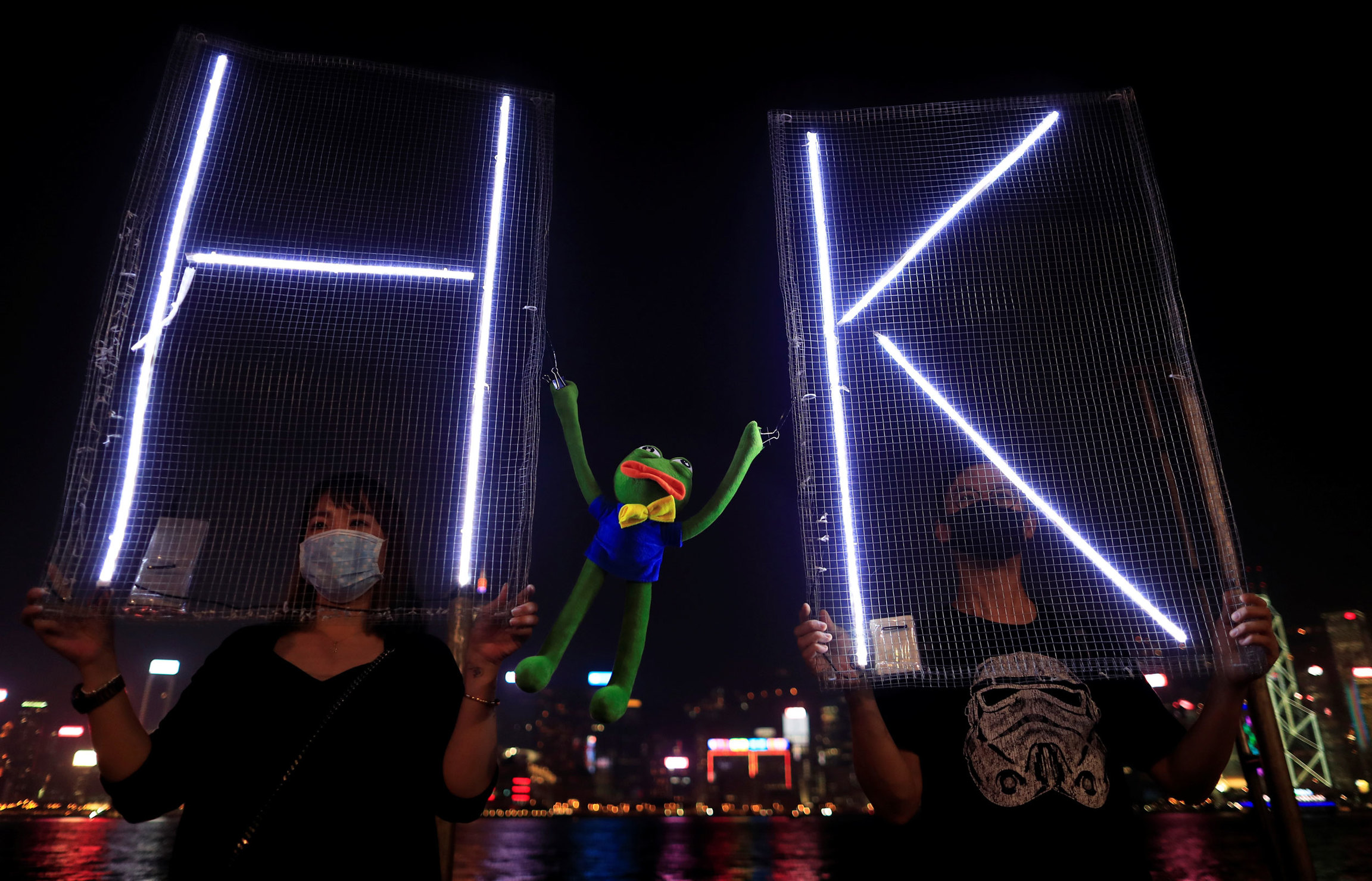 Two people are shown holding signs with electrified letters H and K with a Pepe the Frog plush toy inbetween.