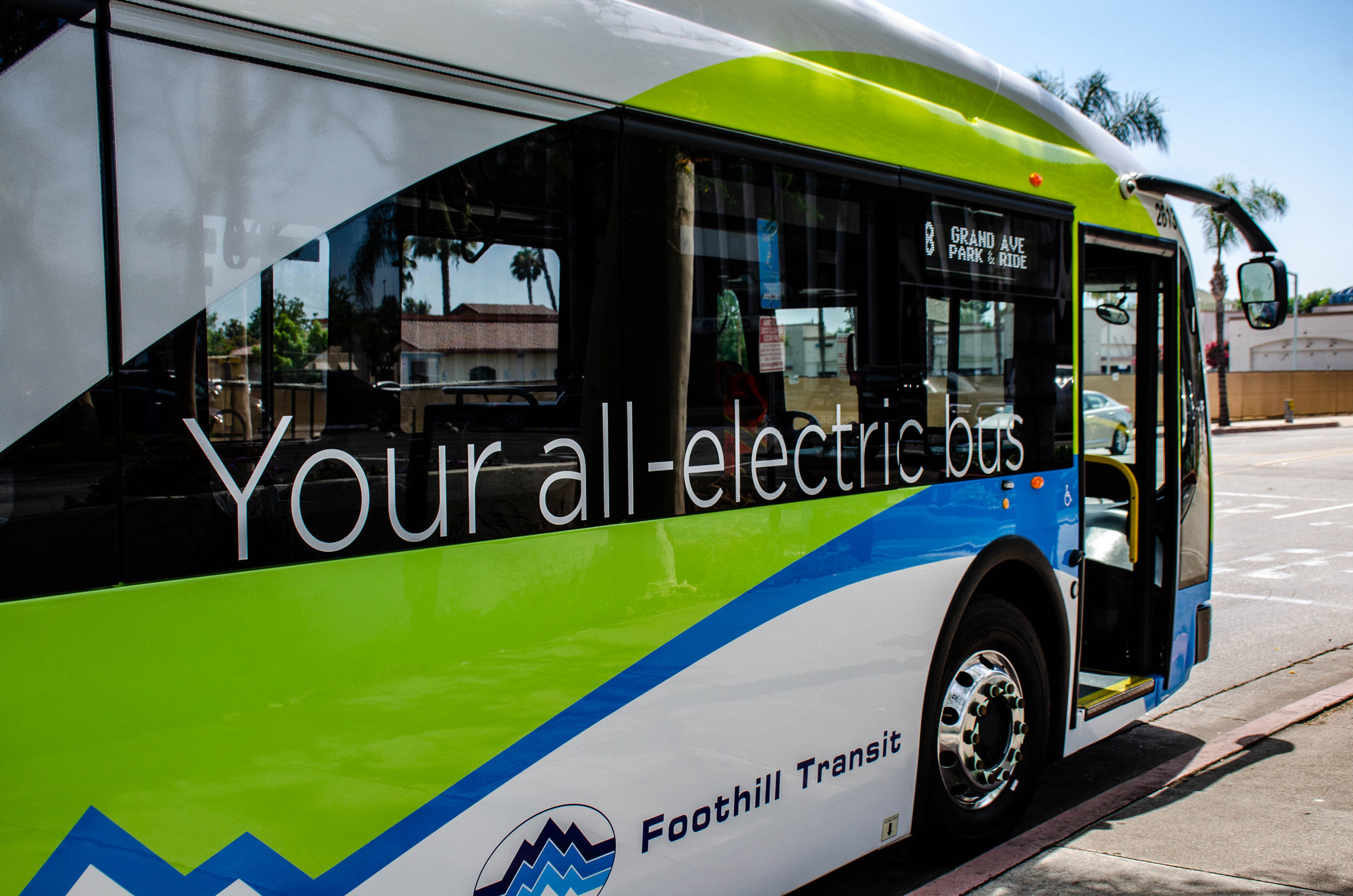 "The side of an electric bus is shown with the words, ""Your all-electric bus,"" printed on the side."