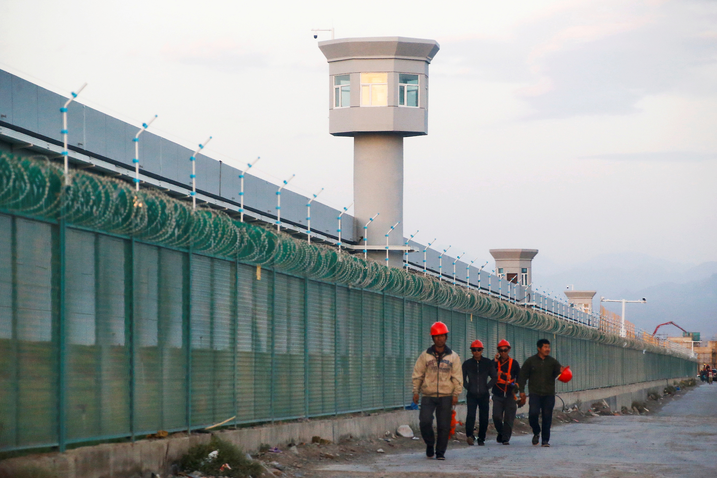 Four workers in uniform walk near a long, green fence.