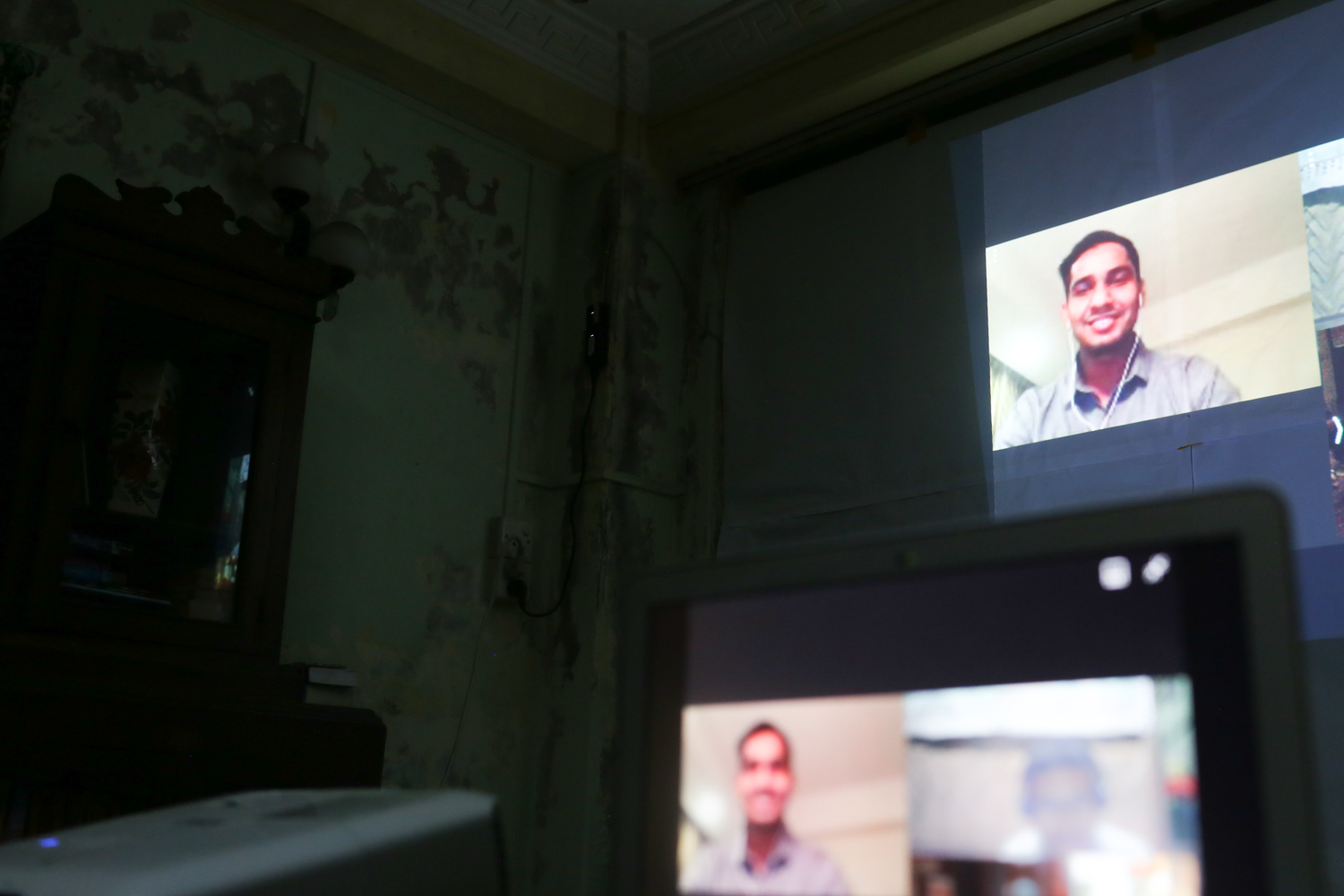 A man appears on a large screen wearing headphones in a video call