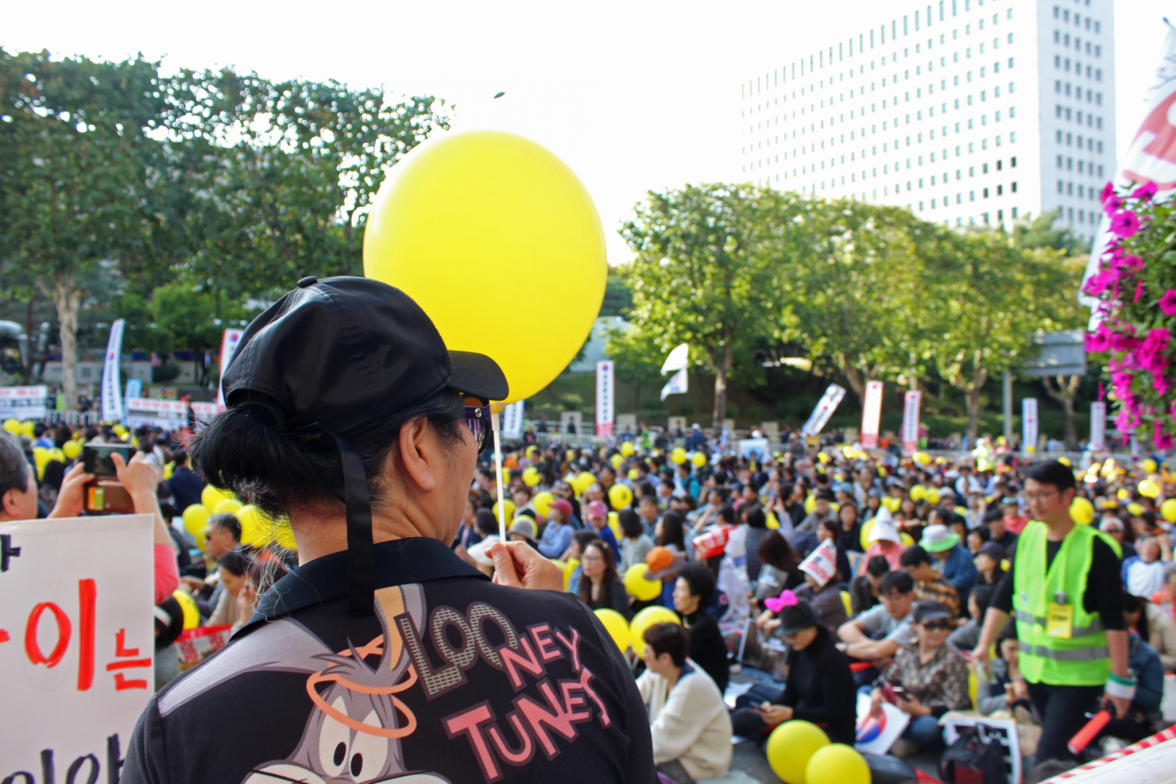 Protesters hold up signs in a protest in South Korea holding yellow balloons