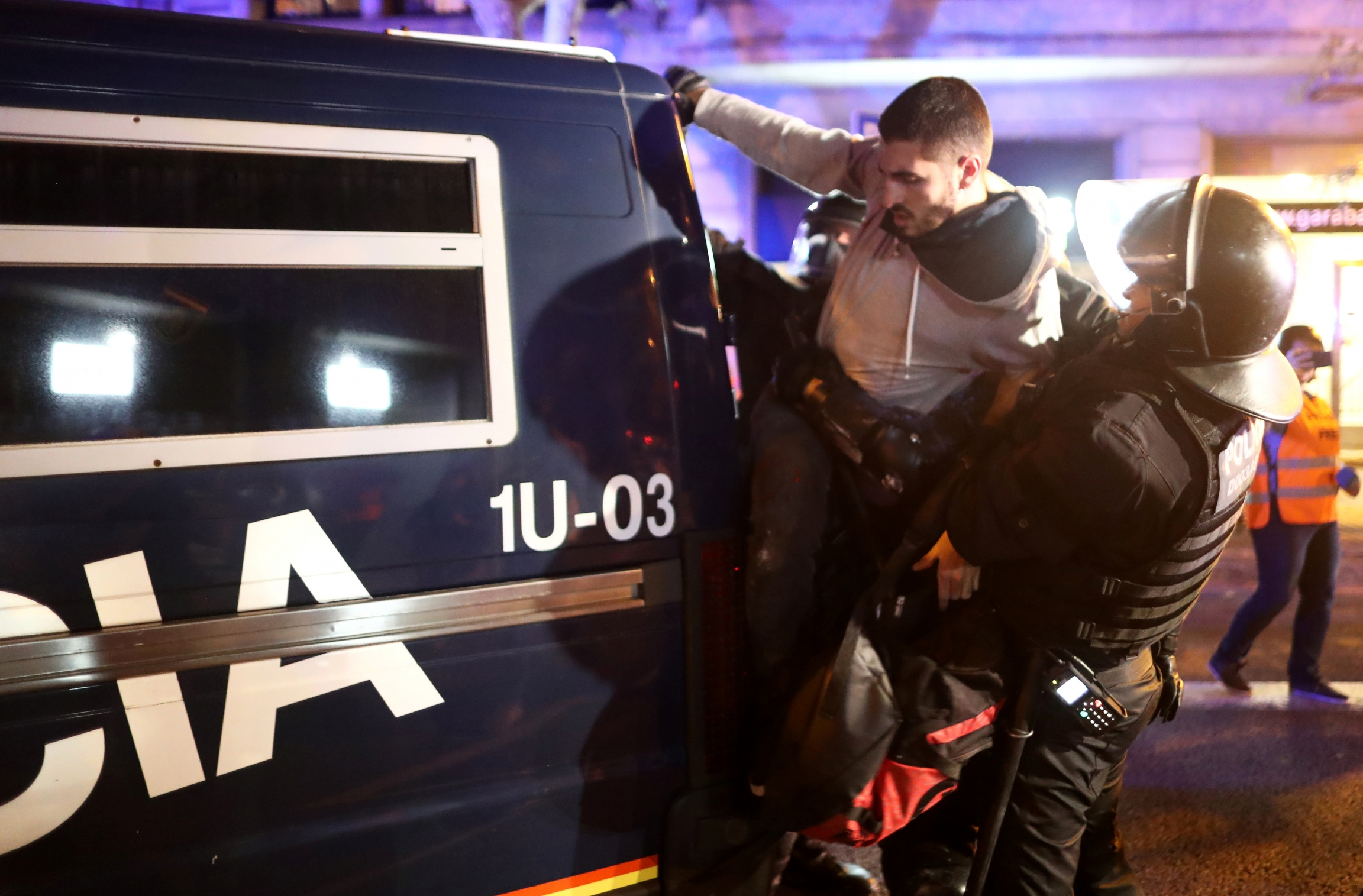 protester detained by police in riot gear
