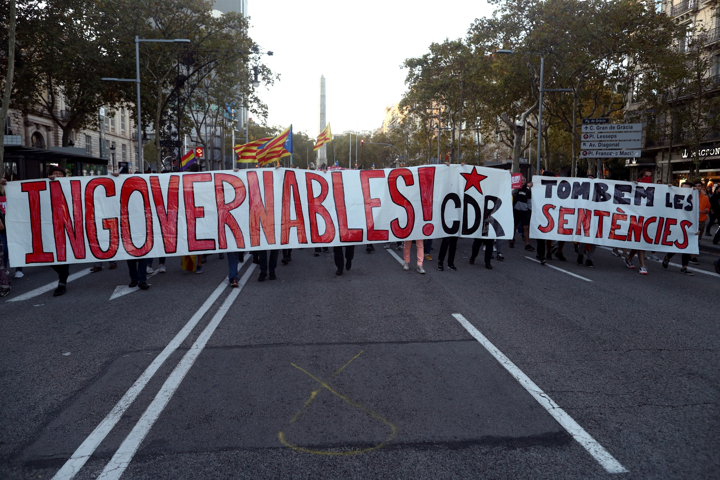 A group of protesters hold a large sign with red lettering on white cloth