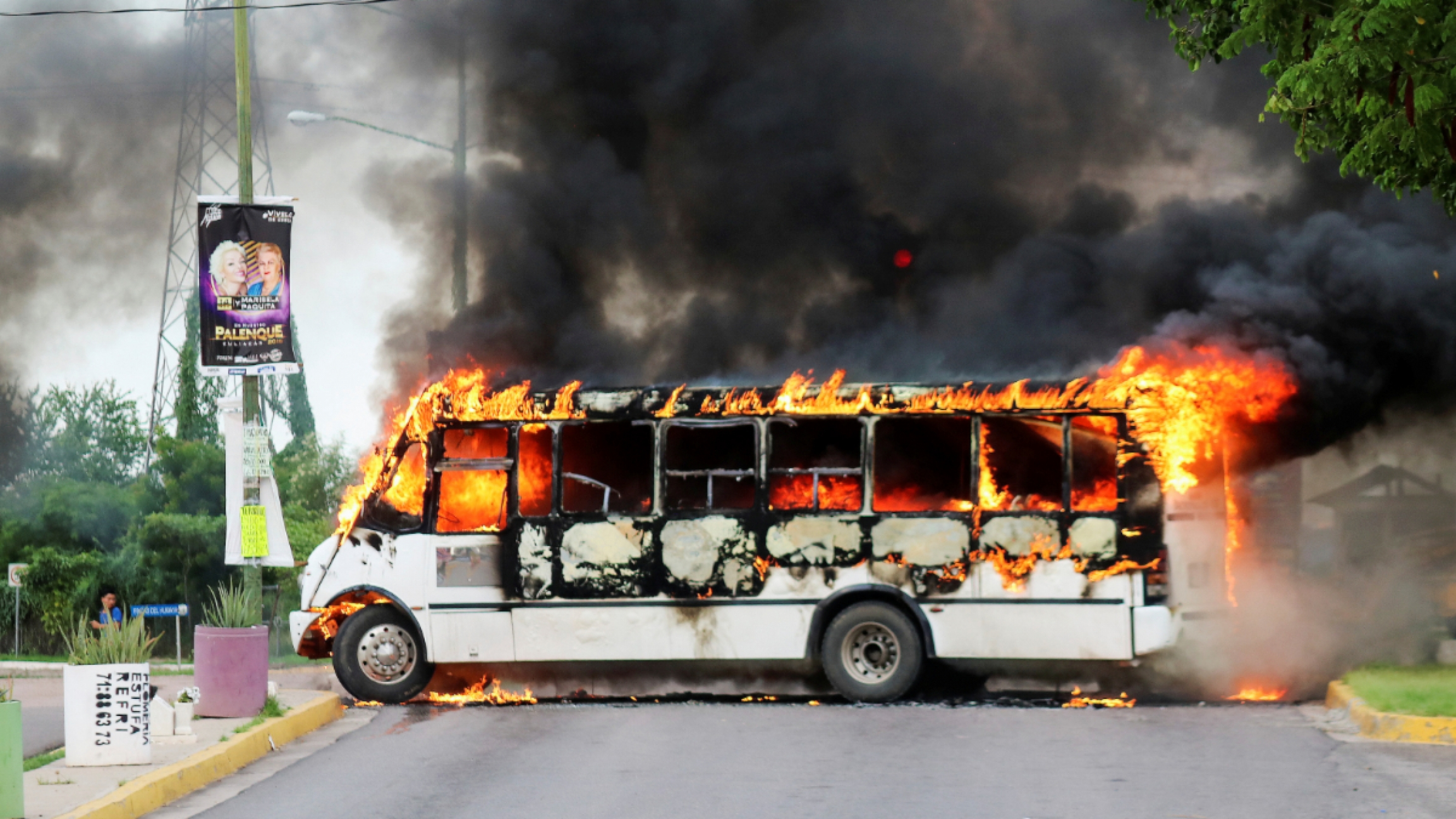 a white bus is engulfed in flames.