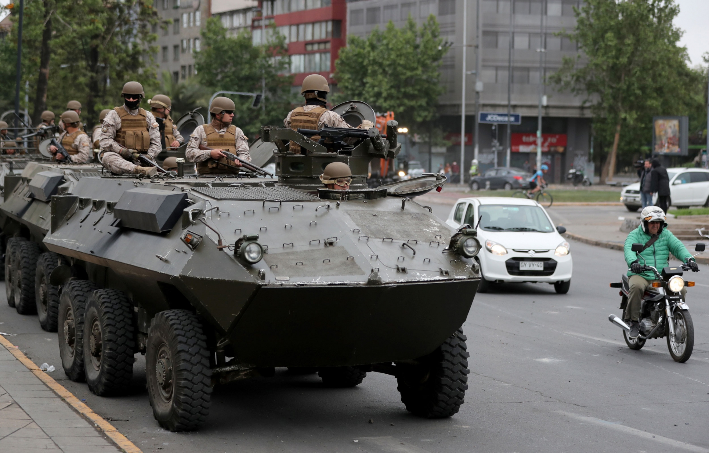 A line of armored transporter trucks are shown with armed soldiers riding on top and a man on a motorcycle passing by.