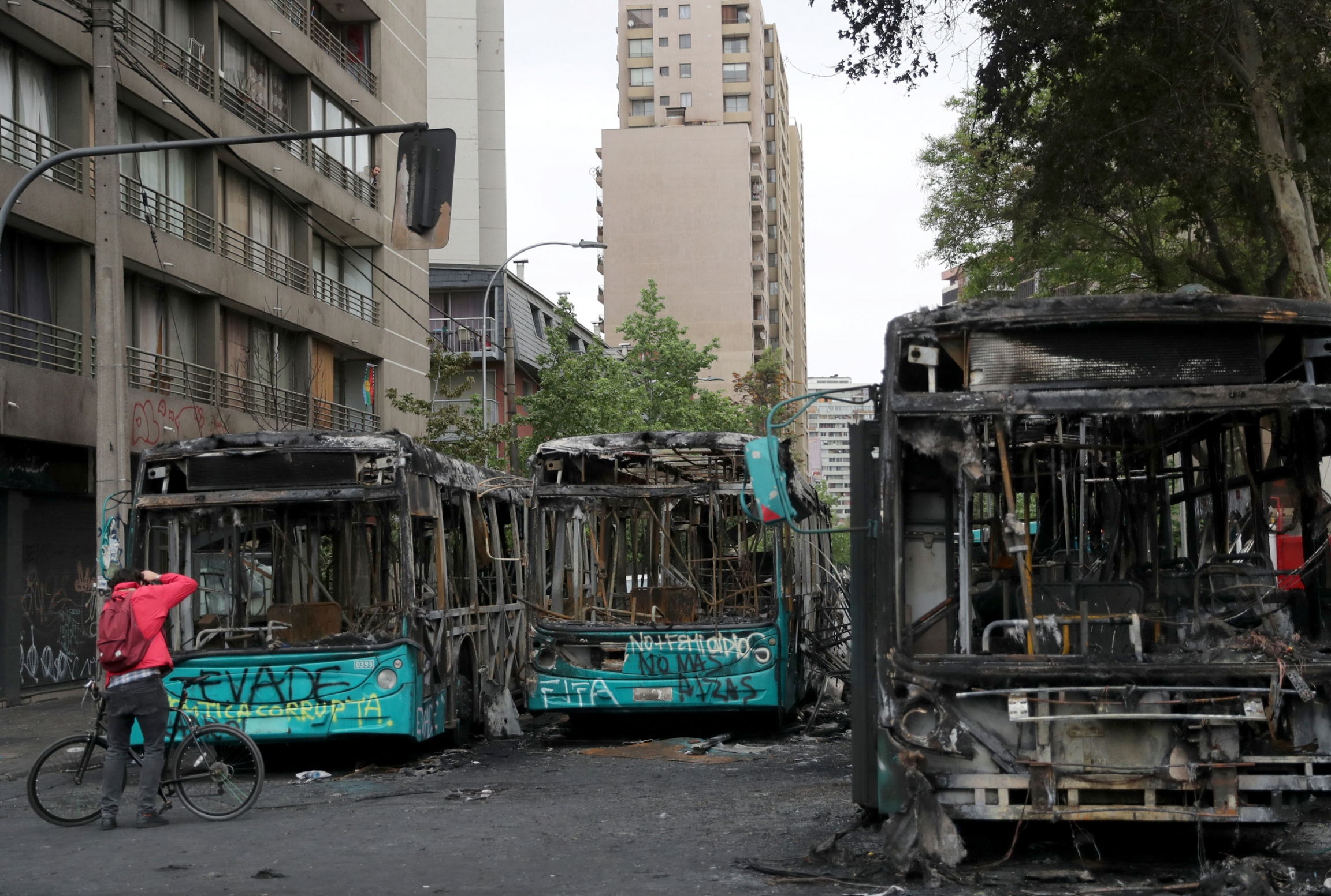 A man is shown with a bicycle standing in front of three totally burned out buses in a street.